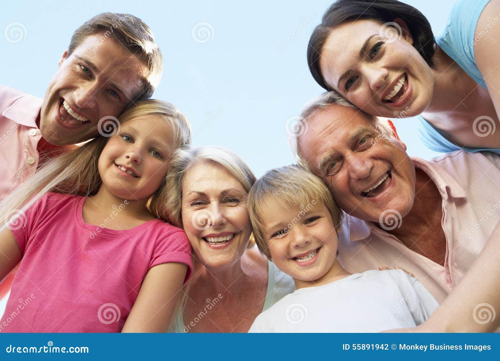 Grupo da família extensa que olha para baixo na câmera