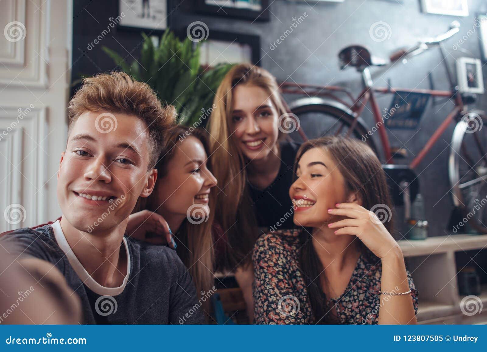 Grupo de adolescentes lindos que toman el selfie con el teléfono móvil mientras que se sienta en un restaurante con el interior e