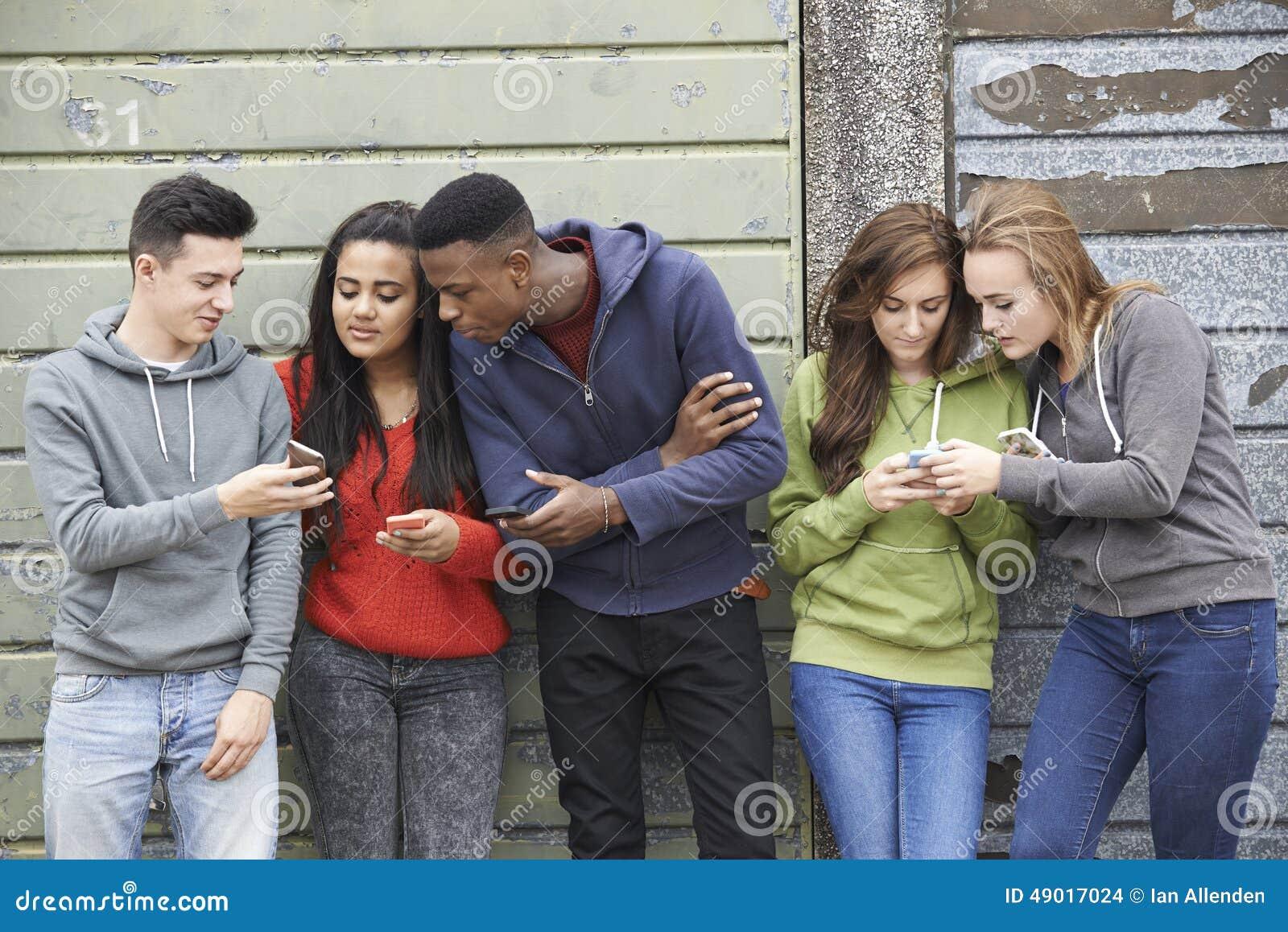 Grupo de adolescentes que comparten el mensaje de texto en los teléfonos móviles