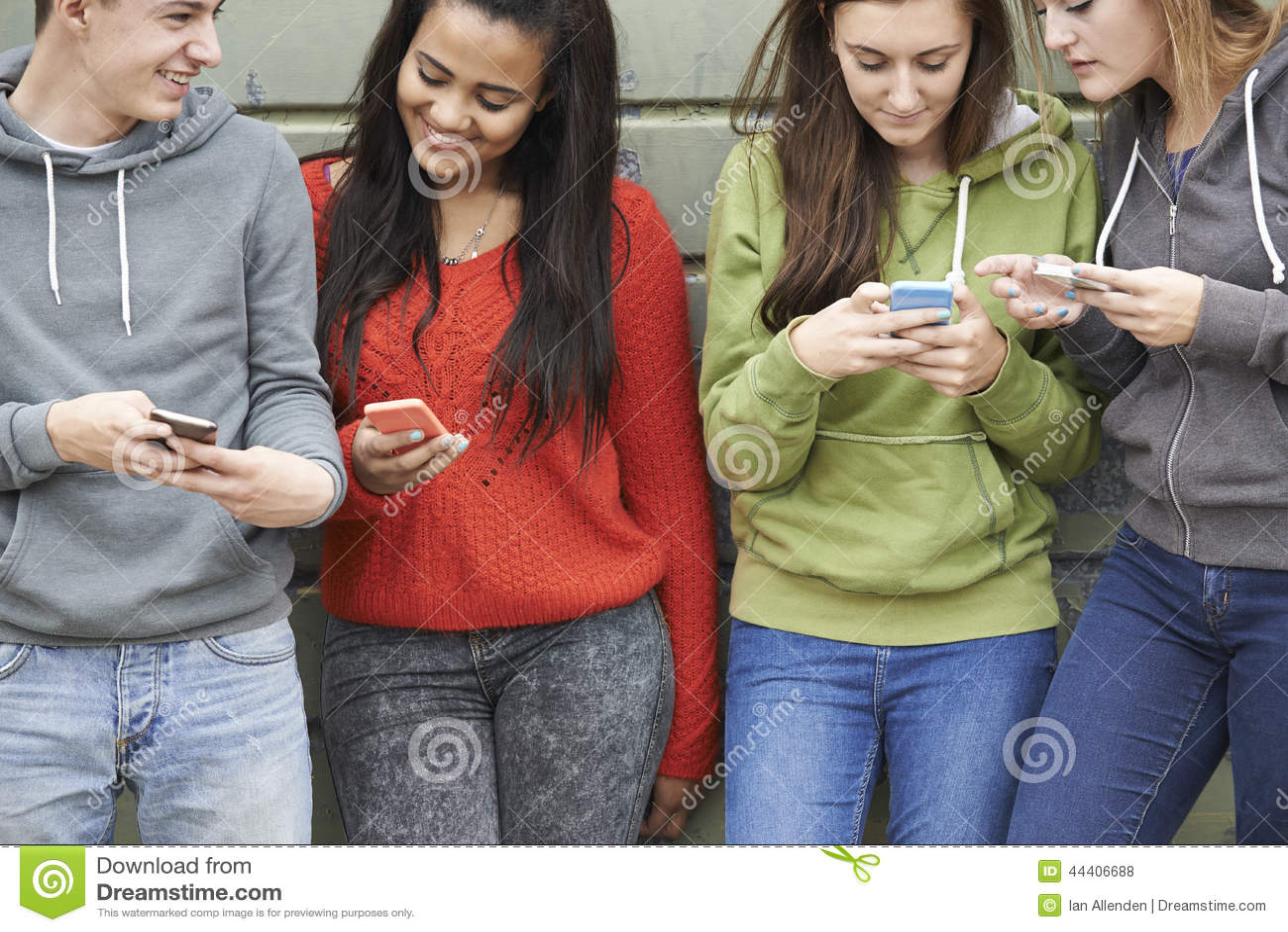 Grupo de adolescentes que compartilham da mensagem de texto em telefones celulares
