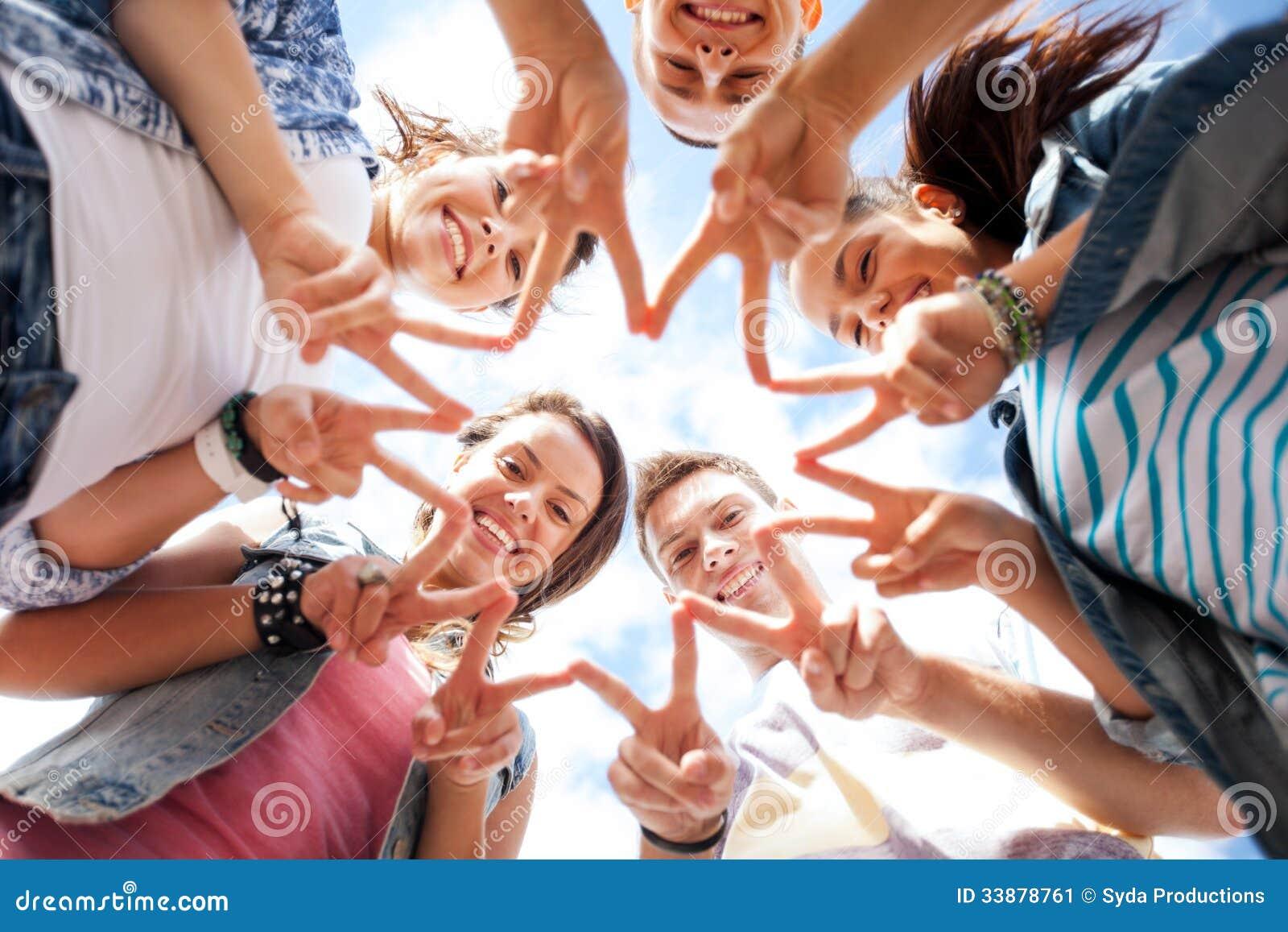 Grupo de adolescentes que mostram o dedo cinco