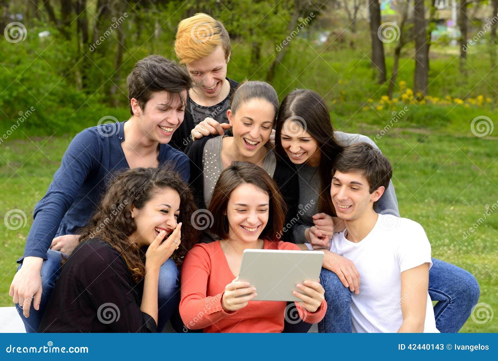 Grupo de adultos jovenes que hojean una tableta y que se divierten