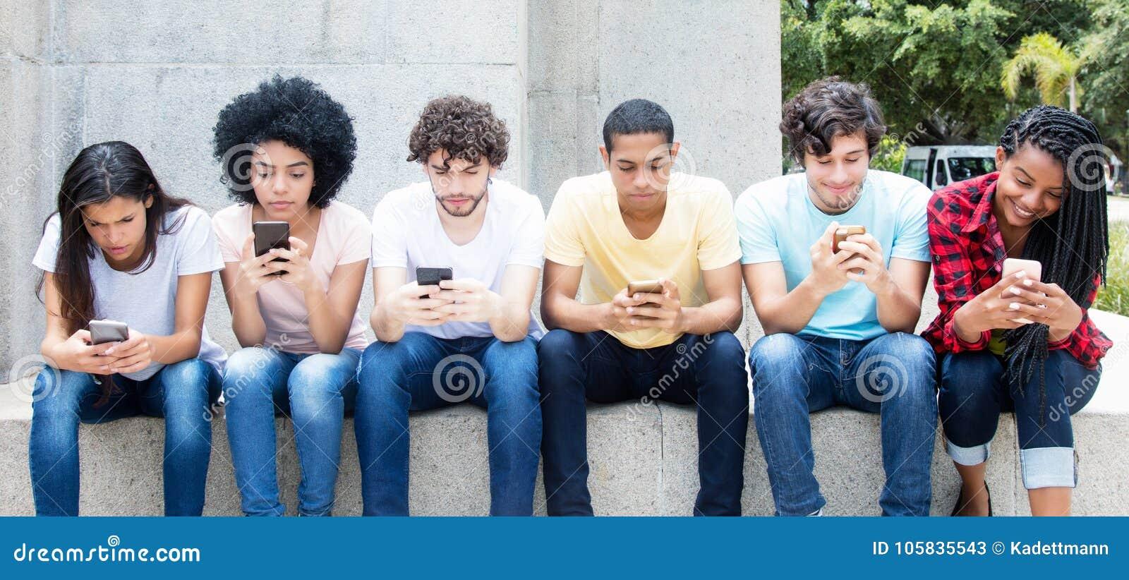 Grupo de adultos jovenes que juegan al juego online con el teléfono