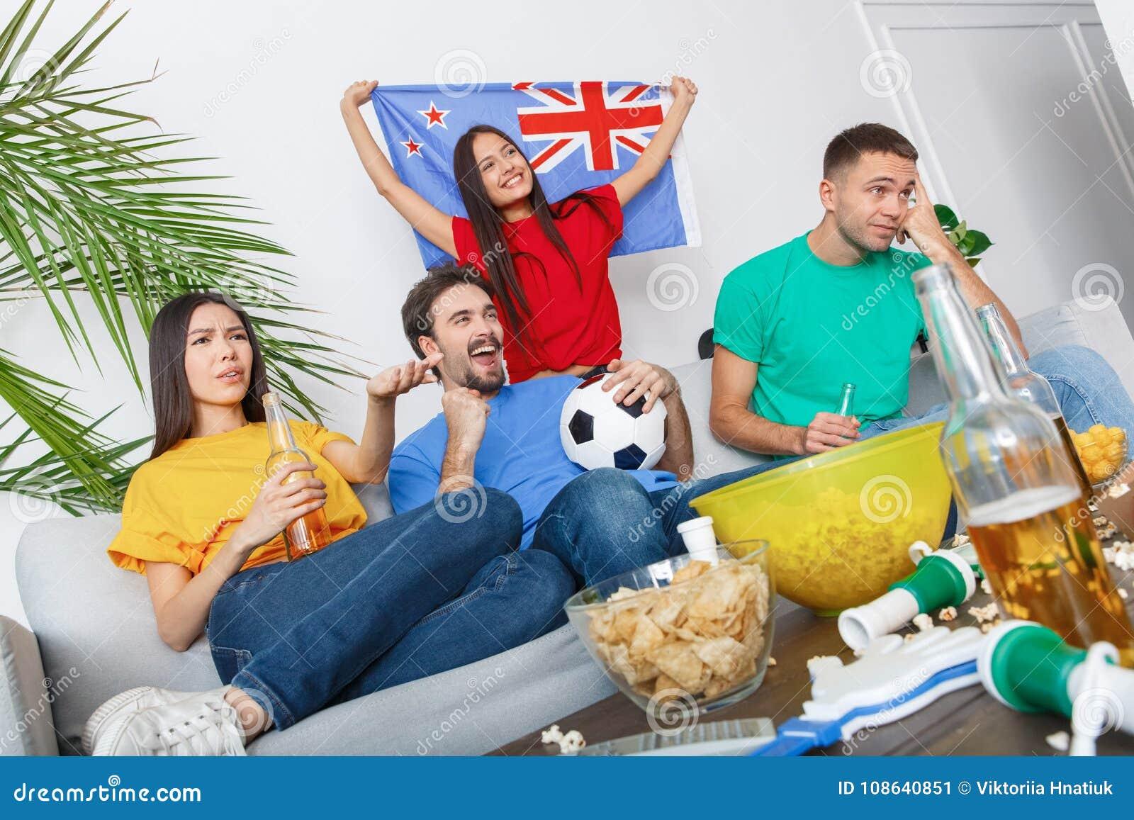 Grupo de aficionados deportivos de los amigos que mira el partido en las camisas coloridas referidas