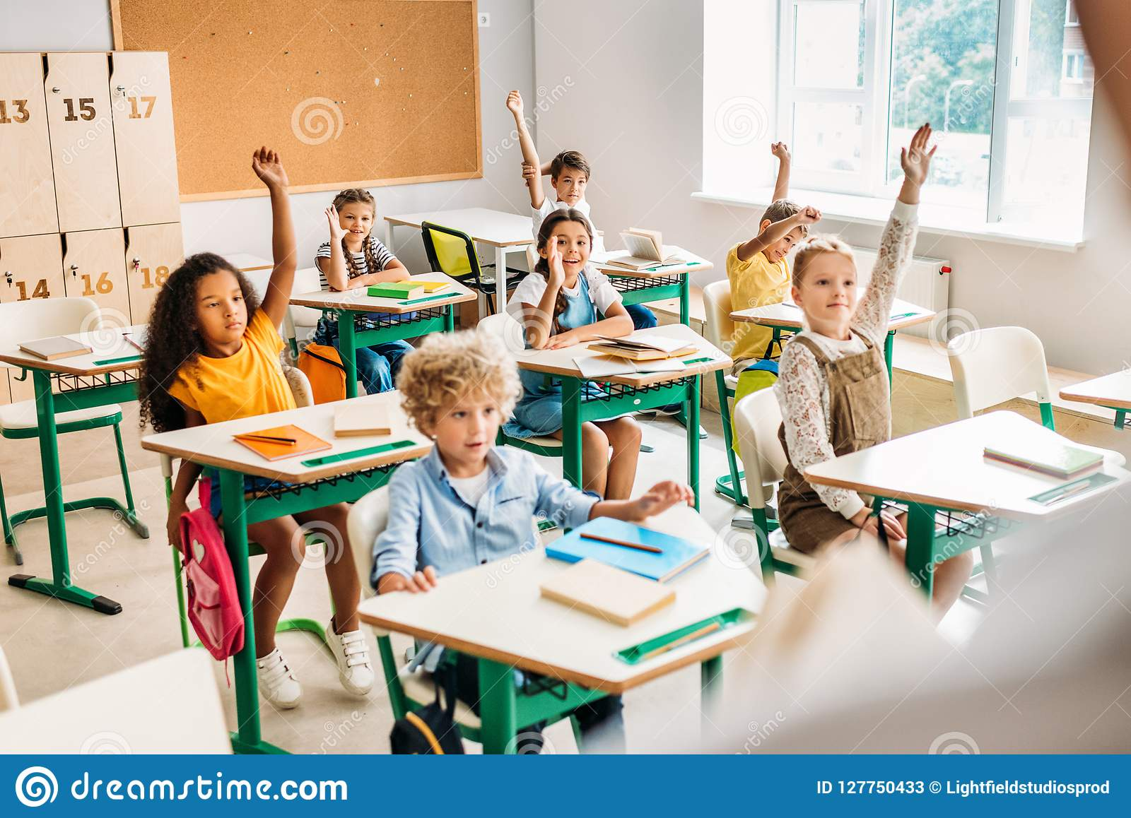 Grupo de alumnos que aumentan las manos para contestar a la pregunta durante la lección