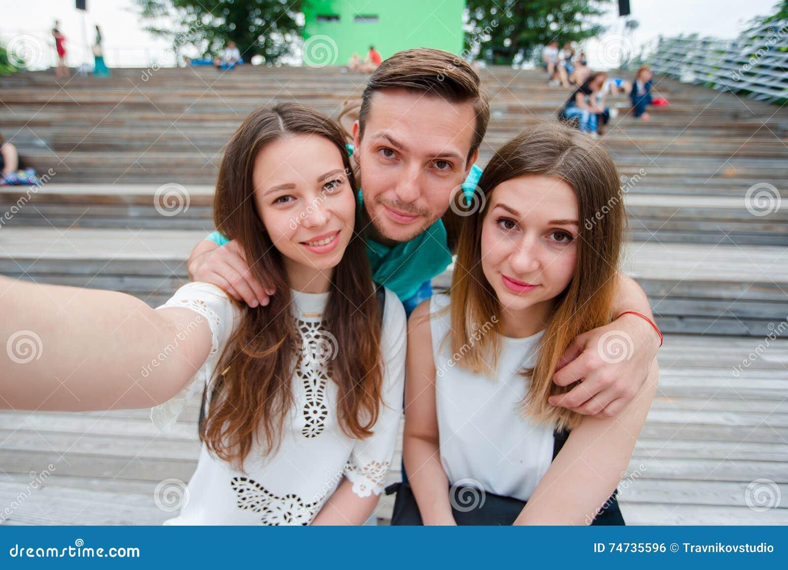 Grupo de amigos adolescentes felizes que riem e que tomam um selfie na rua Três amigos que olham tomando imagens com