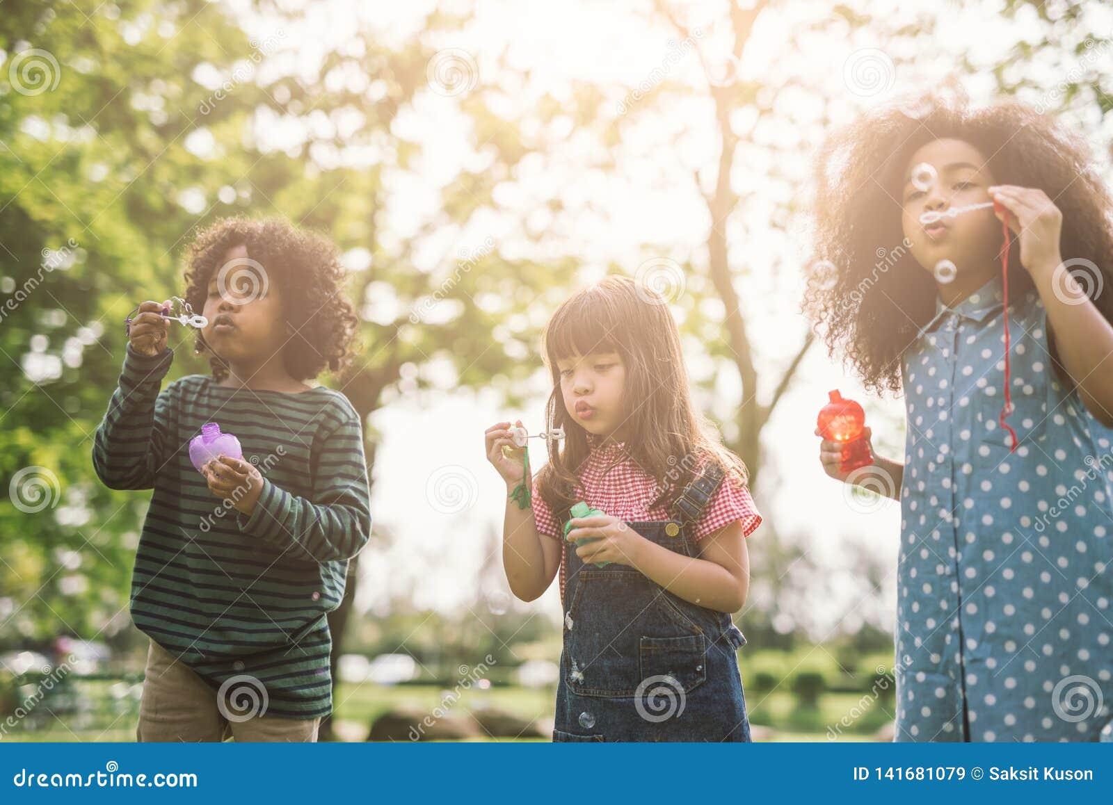 Grupo de amigos bonitos das crianças diversas que têm o divertimento da bolha no gramado verde no parque