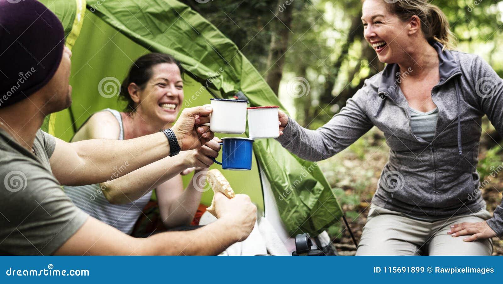 Grupo de amigos diversos que acampan en el bosque