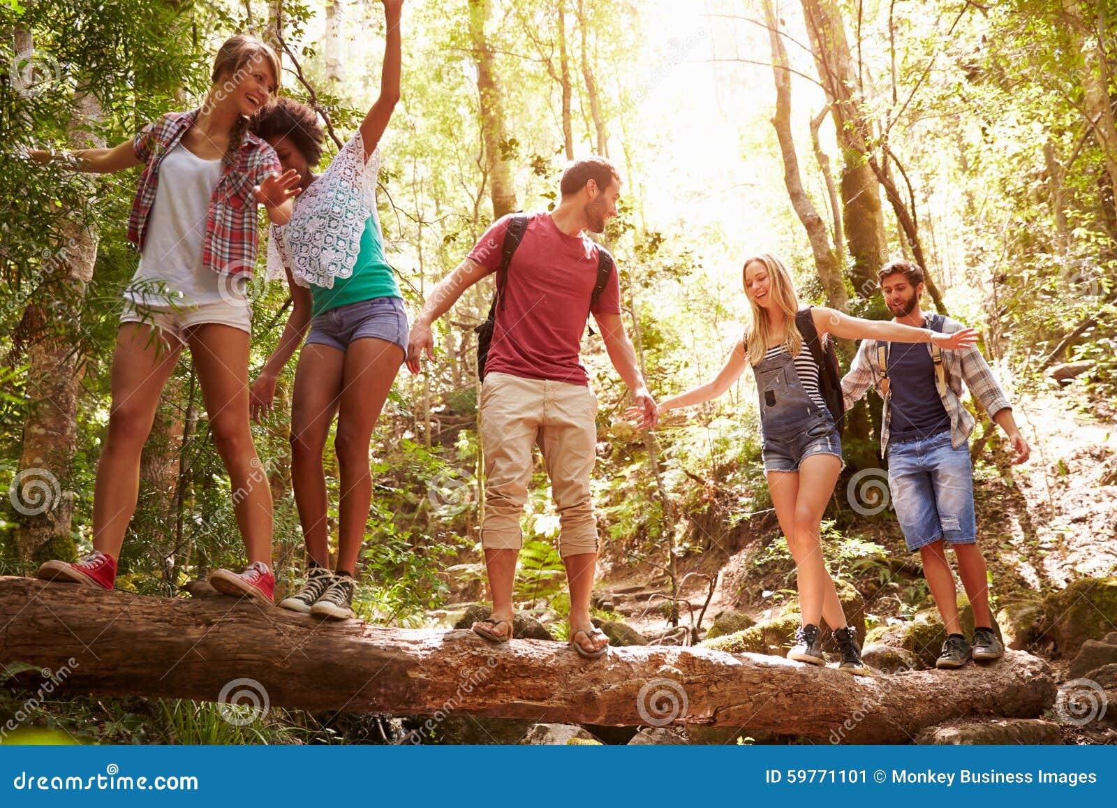 Grupo de amigos en el paseo que equilibra en tronco de árbol en bosque