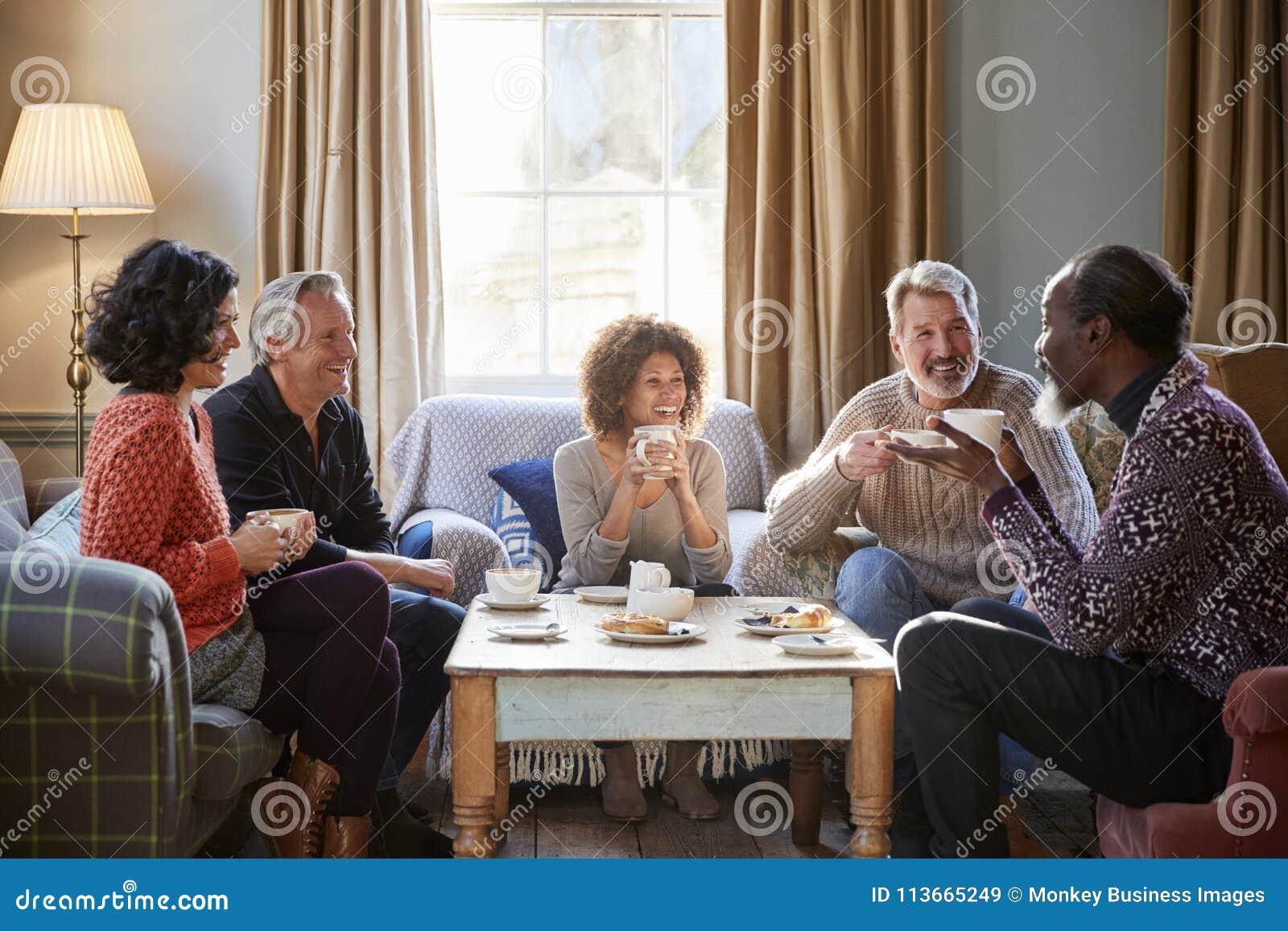 Grupo de amigos envelhecidos meio que encontram-se em torno da tabela na cafetaria