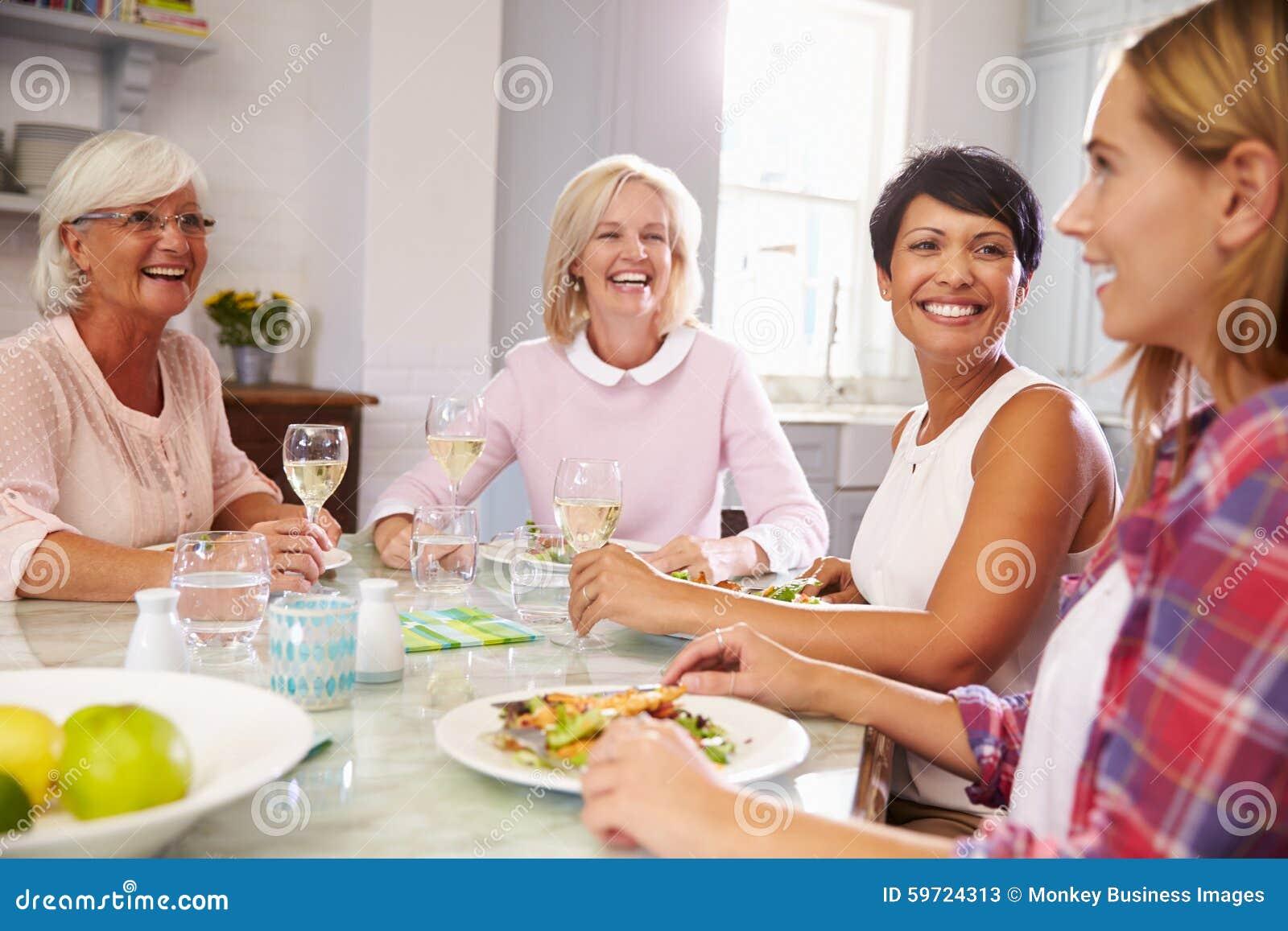 Grupo de amigos fêmeas maduros que apreciam a refeição em casa