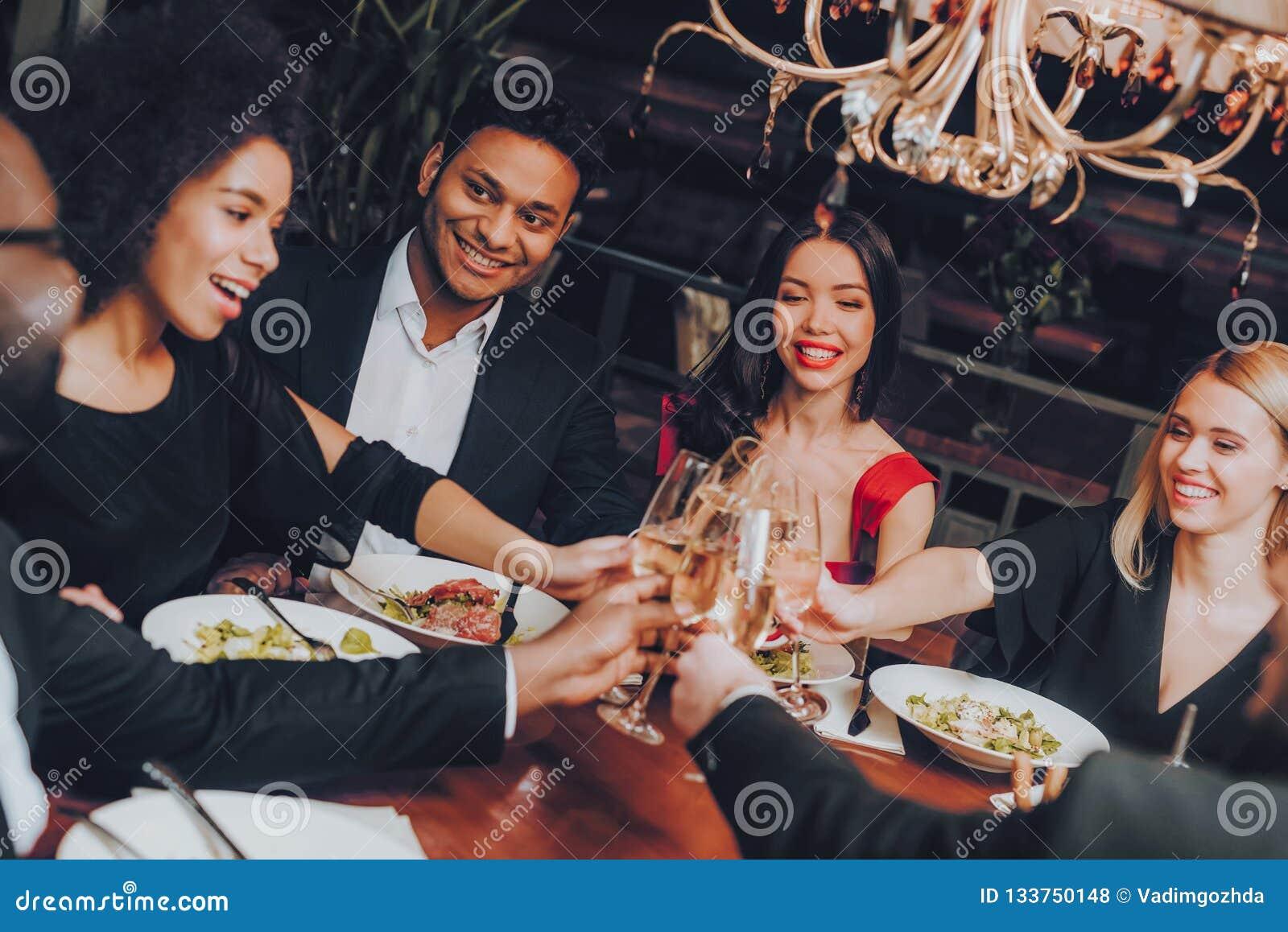 Grupo de amigos felizes que encontram e que têm o jantar