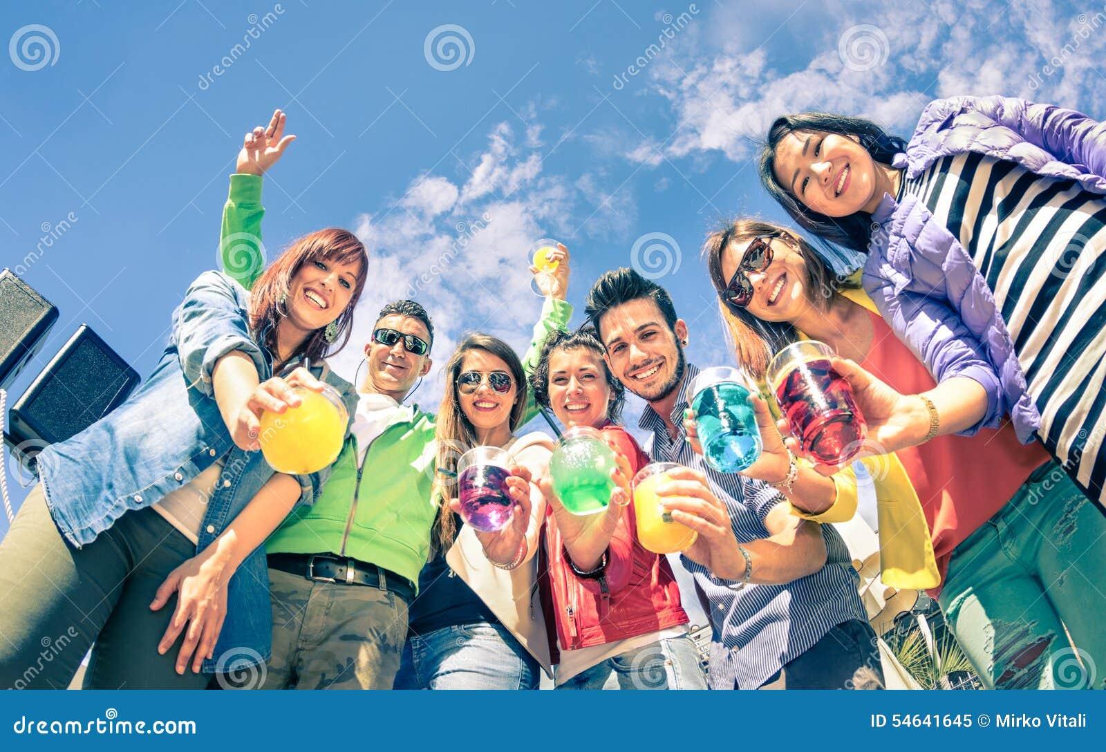 Grupo de amigos felizes que têm o divertimento junto no cocktail