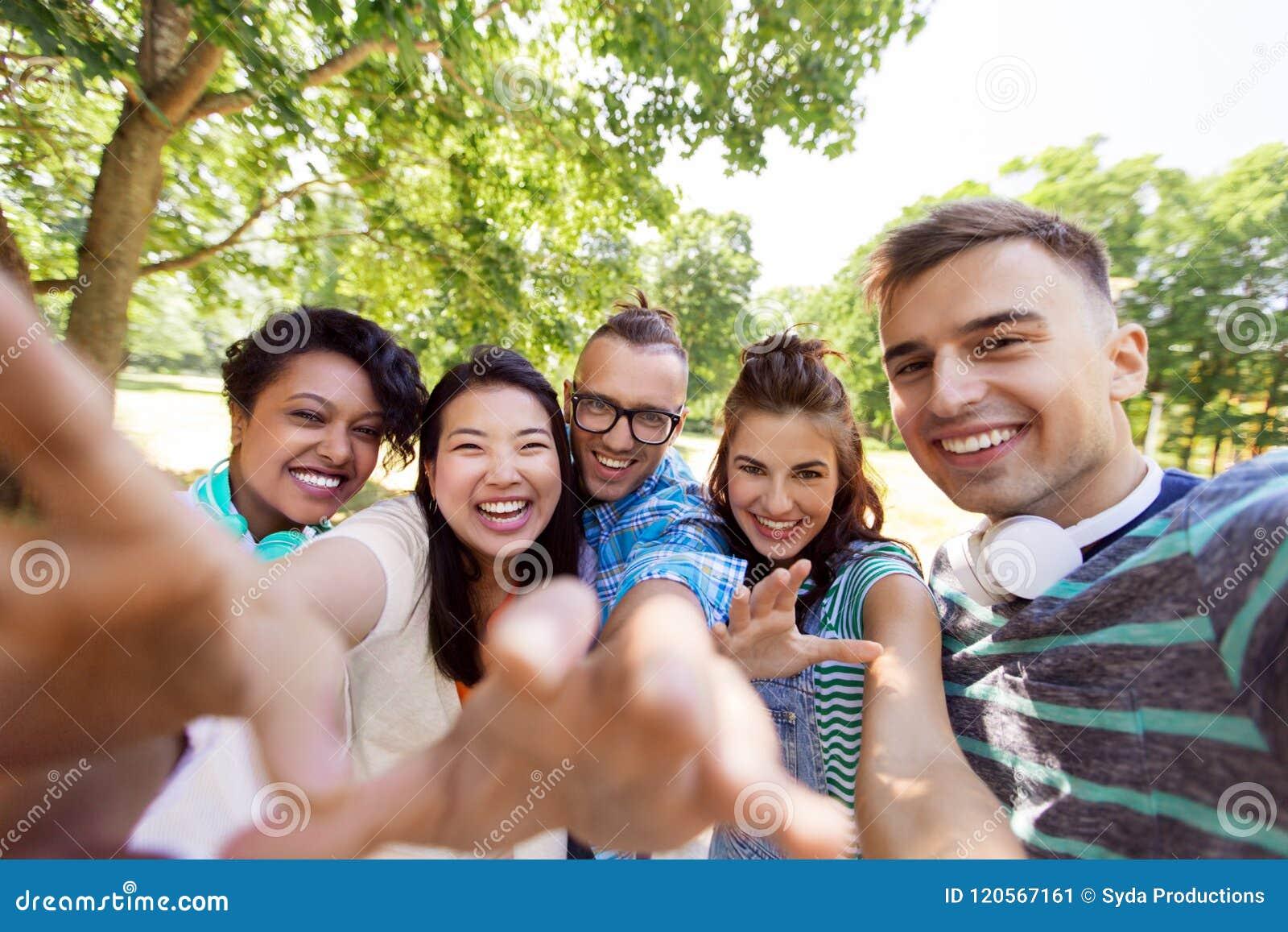 Grupo de amigos internacionales felices que toman el selfie