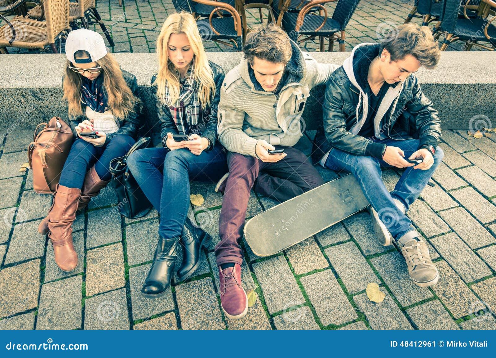 Grupo de amigos jovenes del inconformista que juegan con smartphone