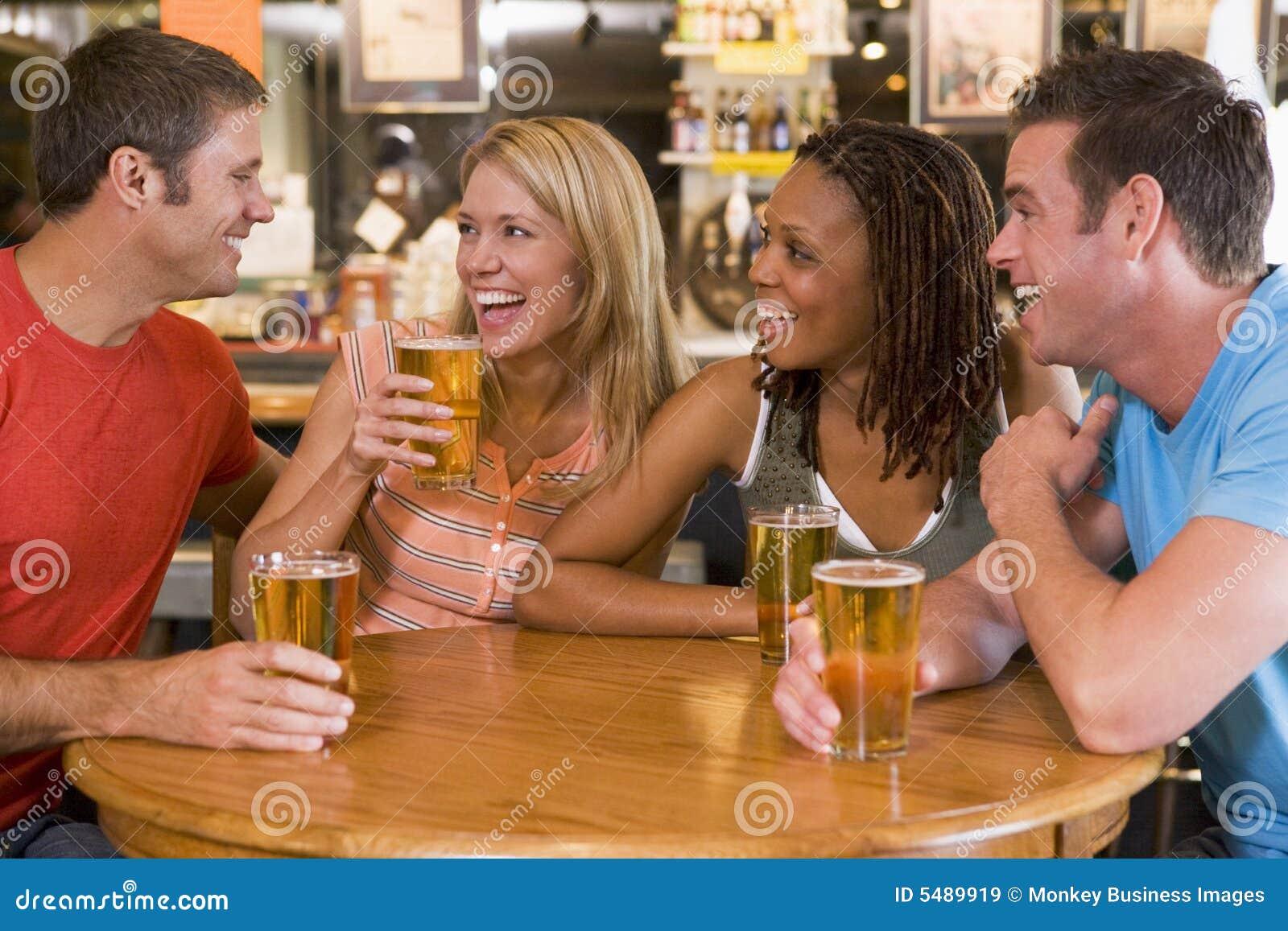 Grupo de amigos jovenes que beben y que ríen