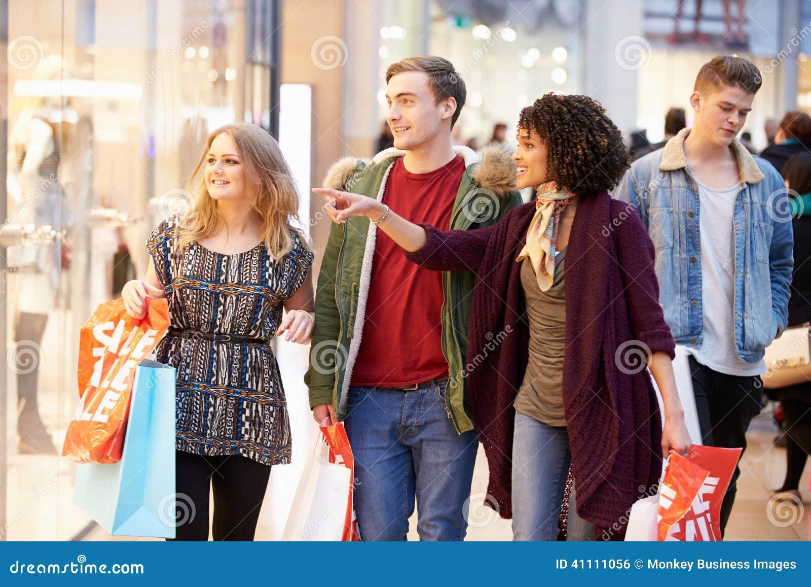 Grupo de amigos jovenes que hacen compras en alameda junto