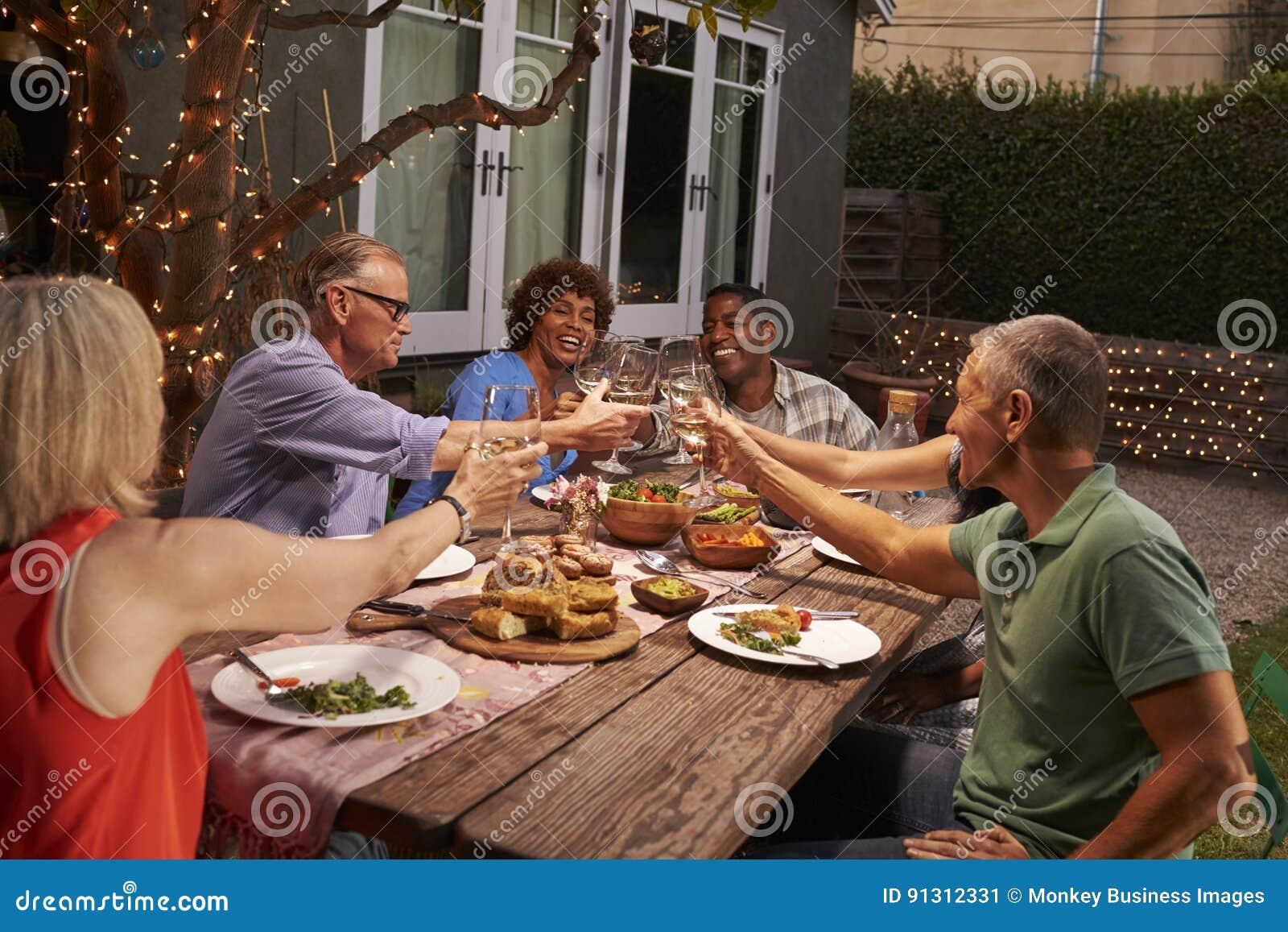 Grupo de amigos maduros que apreciam a refeição exterior no quintal