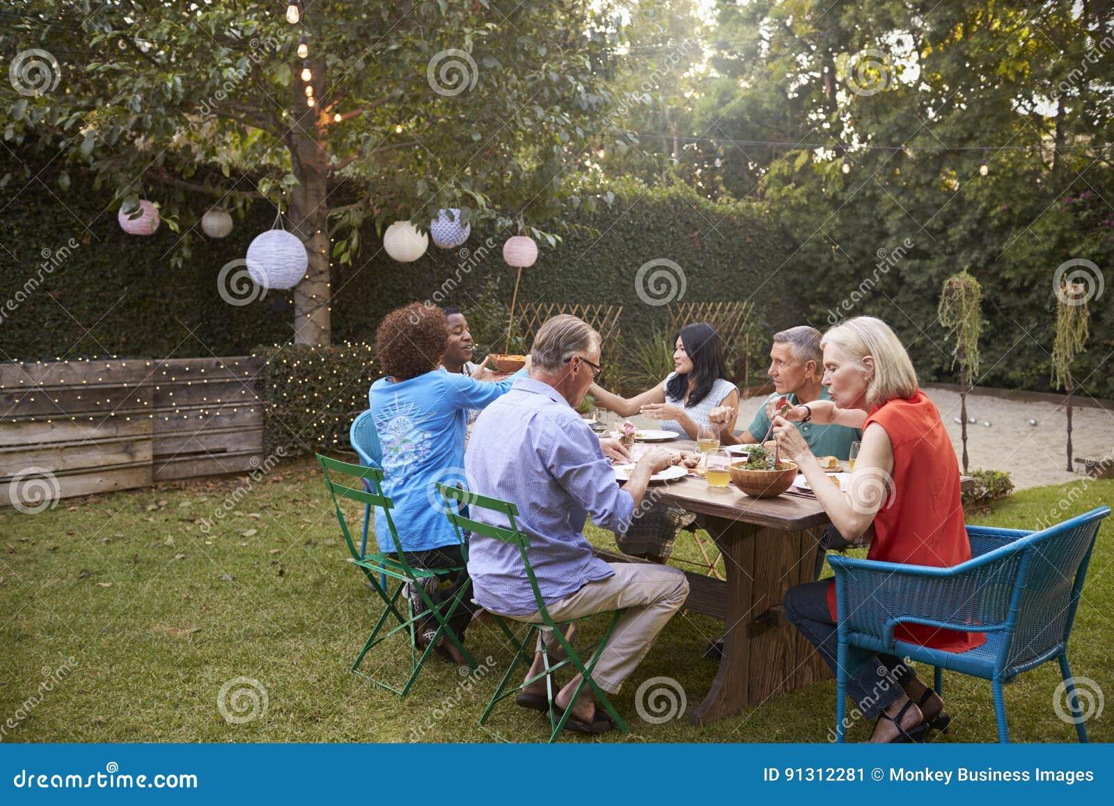 Grupo de amigos maduros que disfrutan de la comida al aire libre en patio trasero