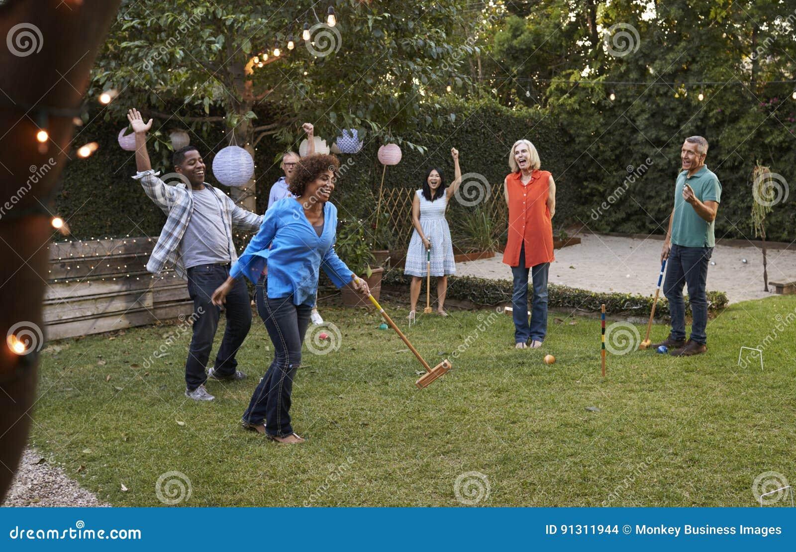 Grupo de amigos maduros que jogam o cróquete no quintal junto