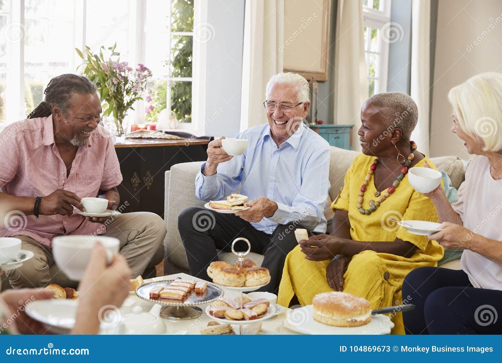 Grupo de amigos mayores que gozan de té de tarde en casa junto