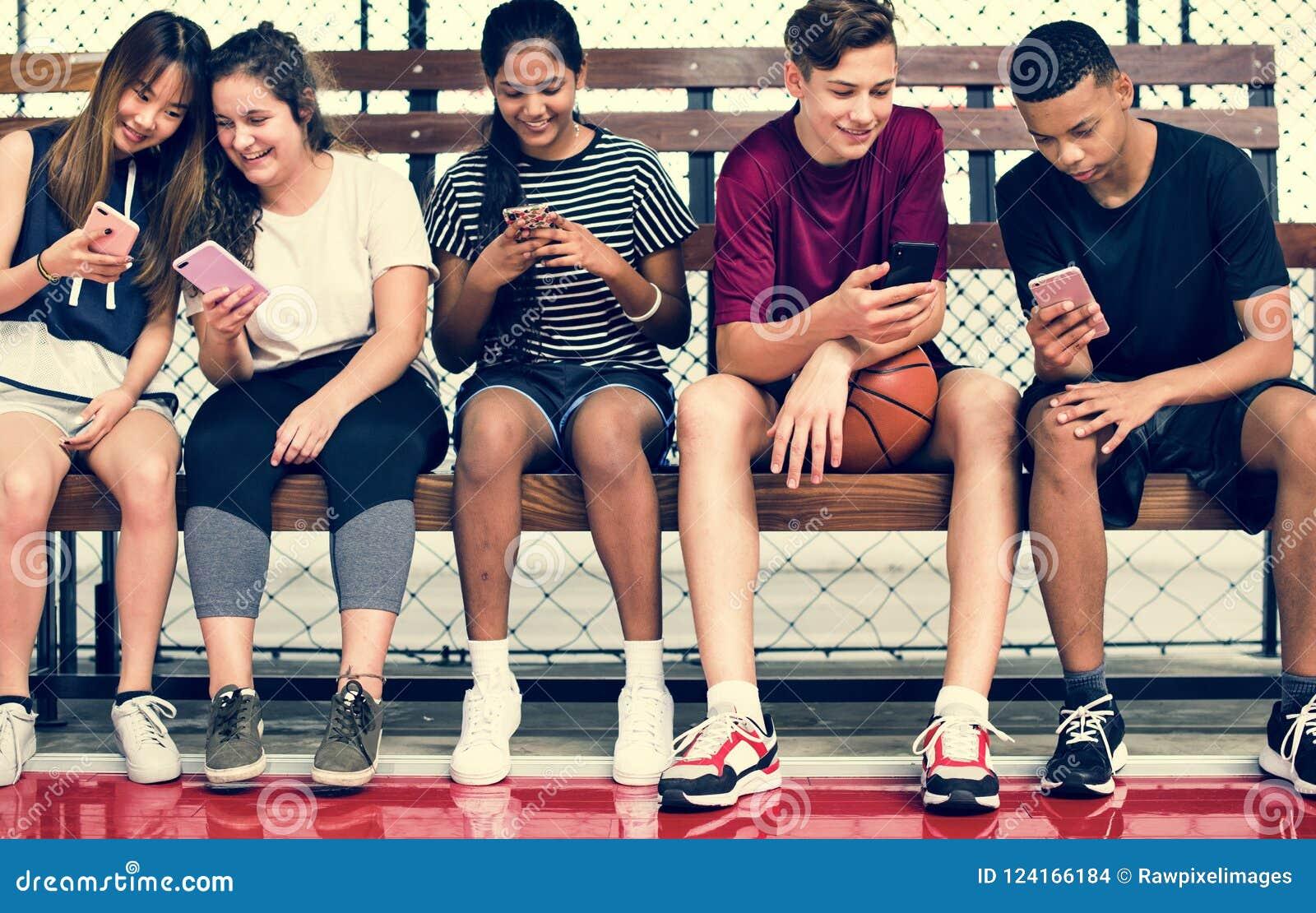 Grupo de amigos novos do adolescente em um campo de básquete que relaxa usando o smartphone