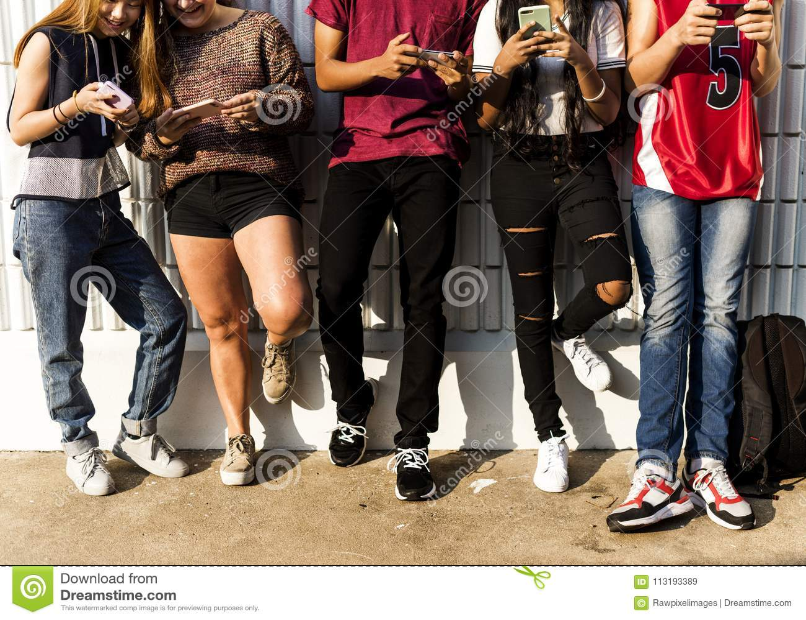 Grupo de amigos novos do adolescente que refrigeram para fora junto usando o conceito social dos meios do smartphone
