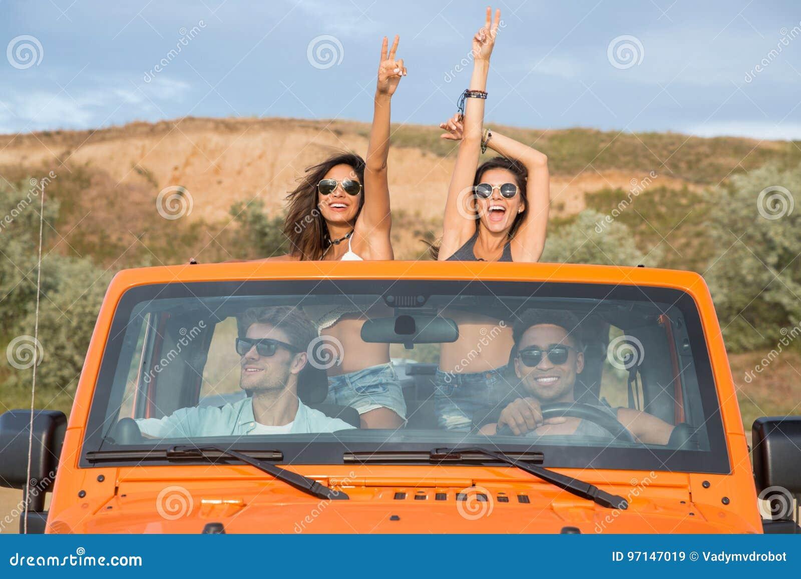 Grupo de amigos novos entusiasmado que estão em um carro com as mãos levantadas