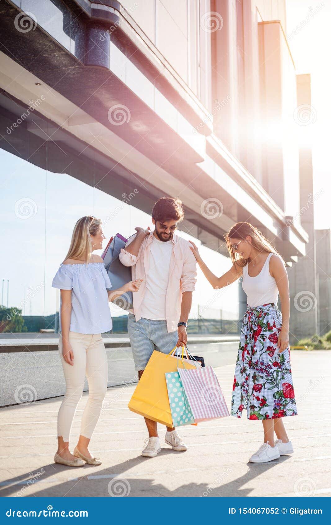 Grupo de amigos novos felizes que retornam da compra