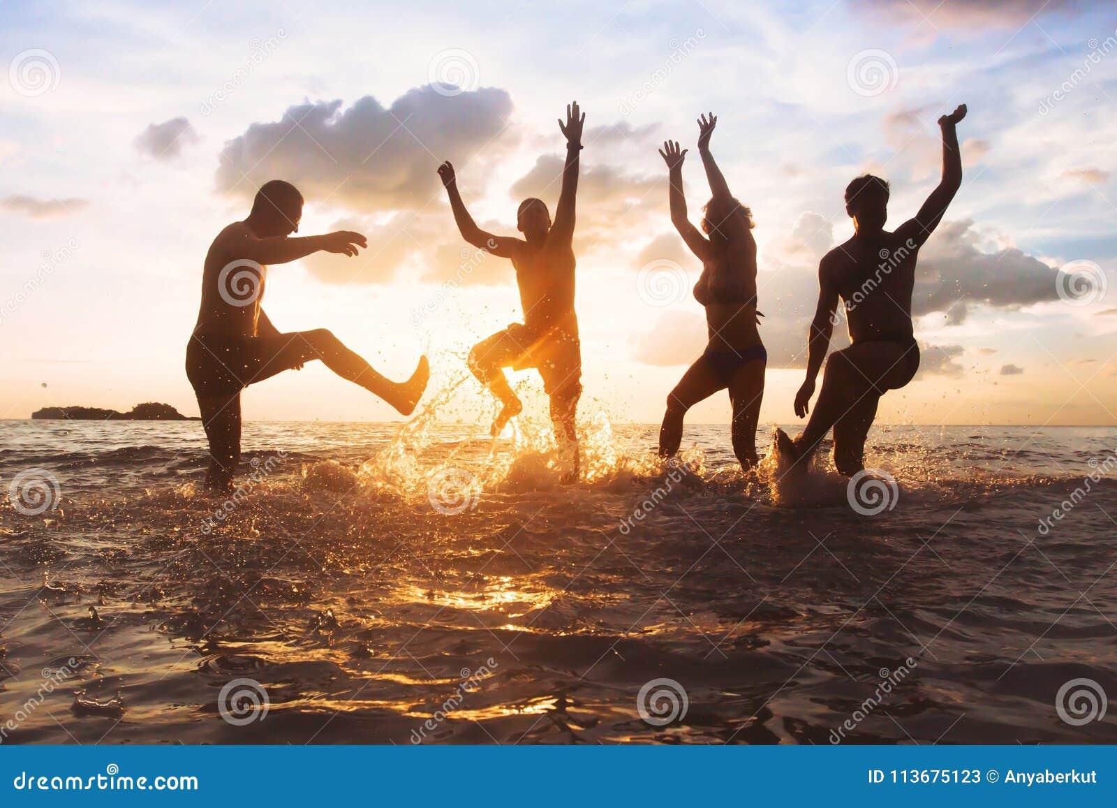 Grupo de amigos ou de família feliz que têm o divertimento junto na praia no por do sol, no salto e na dança