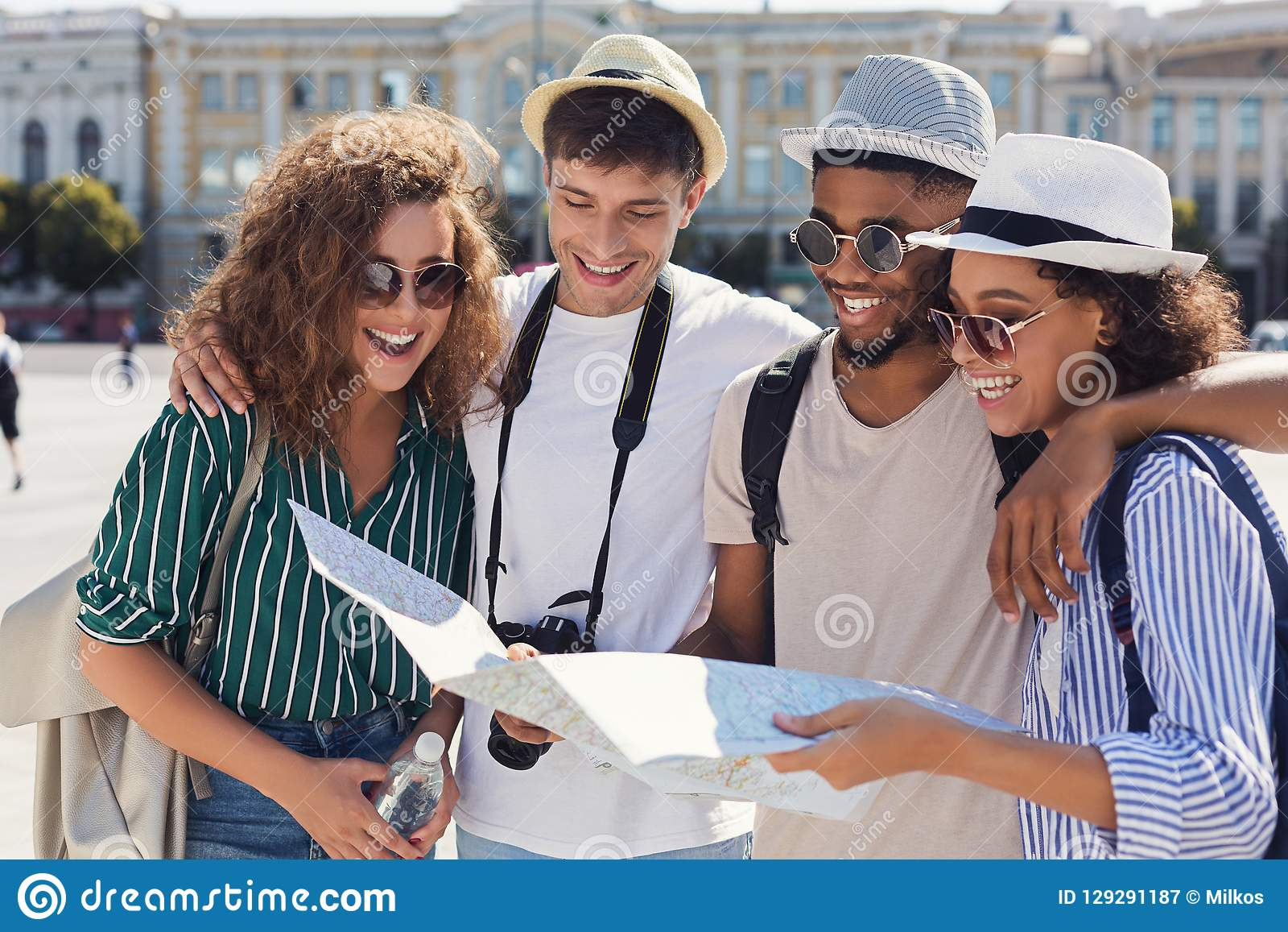 Grupo de amigos que caminan a través de la ciudad con el mapa
