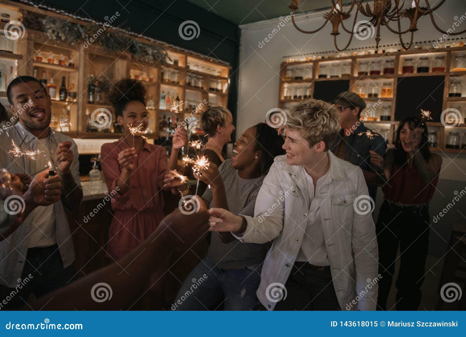 Grupo de amigos que celebran con las bengalas en una barra