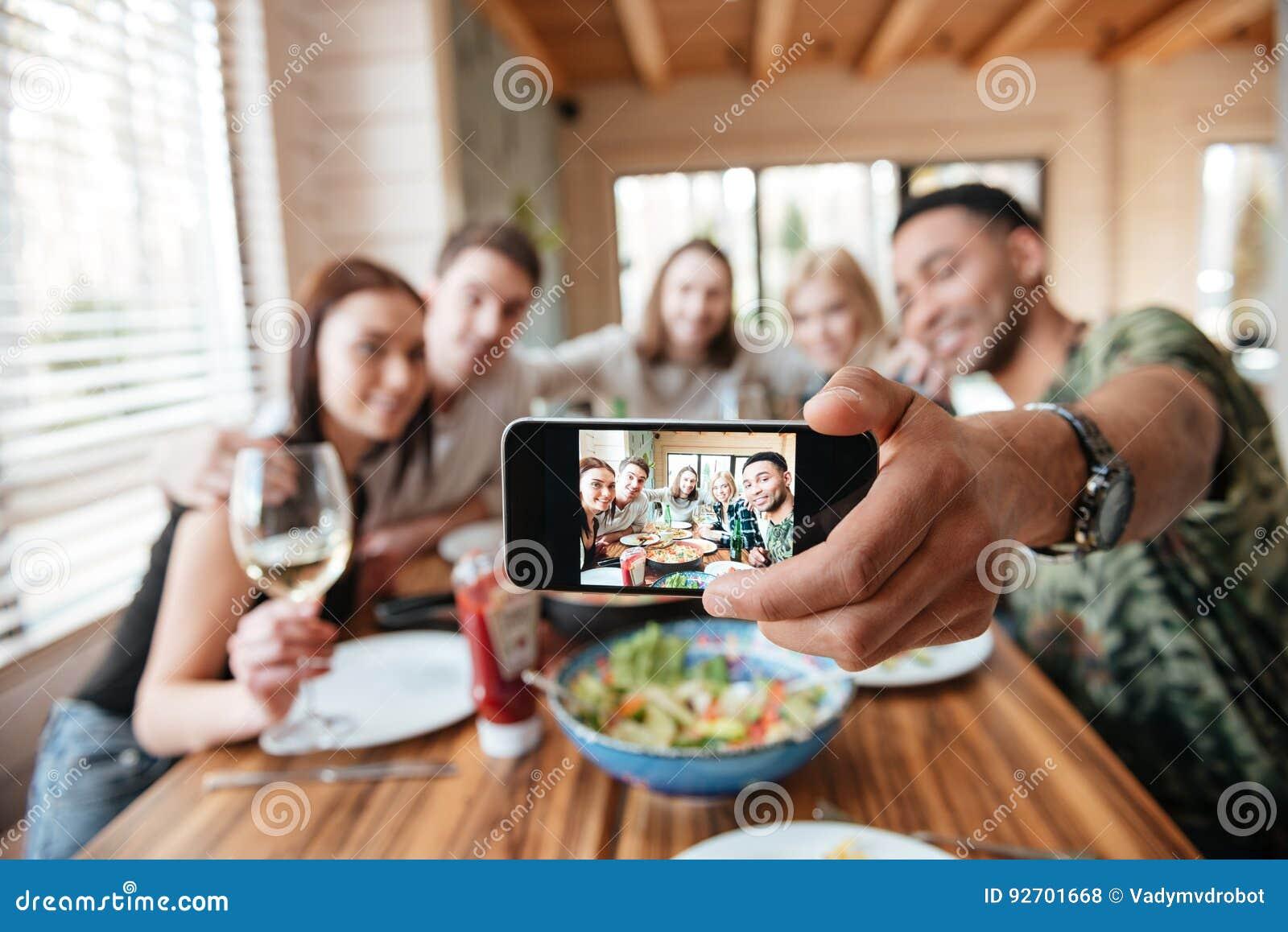 Grupo de amigos que cenan y que toman el selfie con smartphone