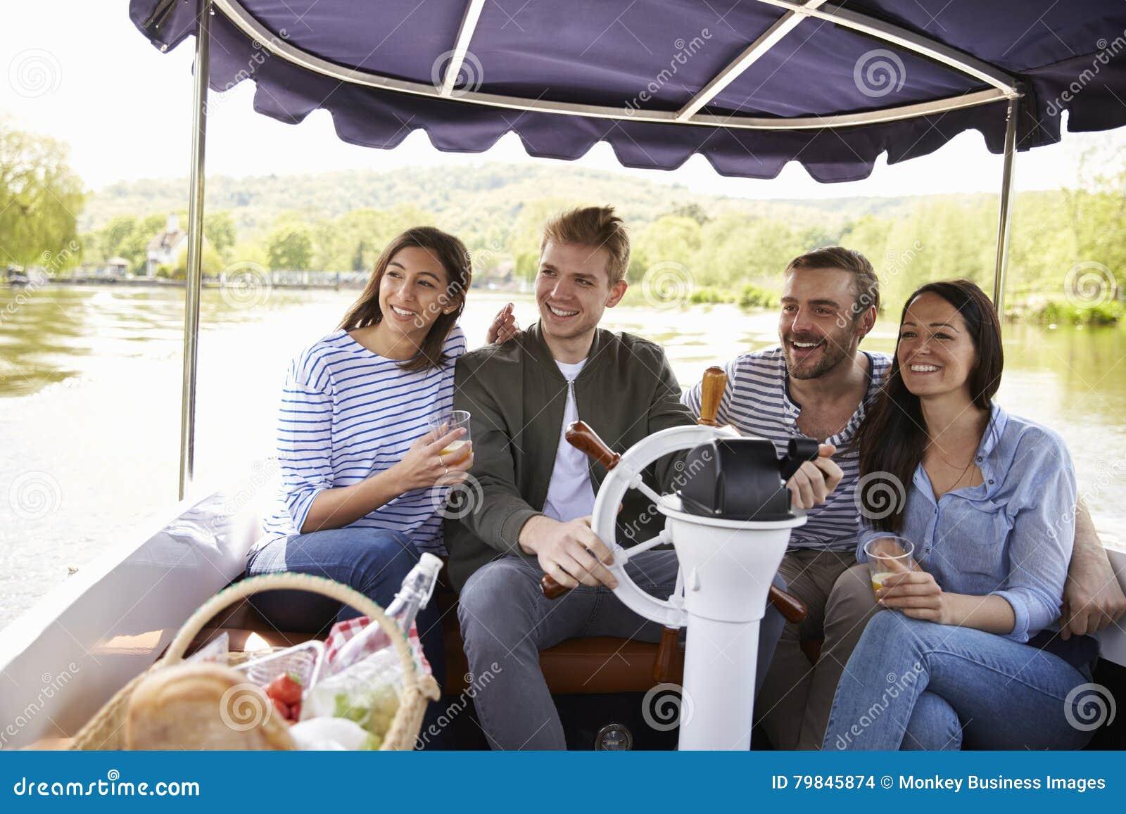 Grupo de amigos que disfrutan de día hacia fuera en barco en el río junto