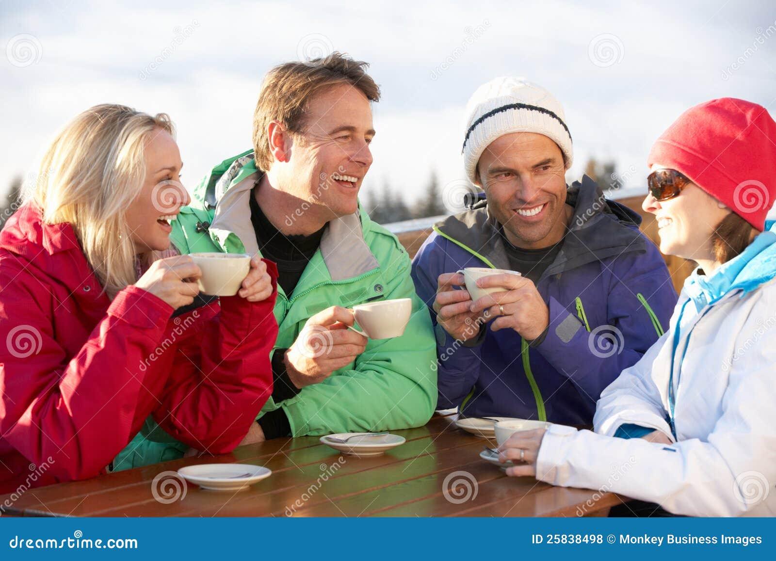 Grupo de amigos que disfrutan de la bebida caliente en la estación de esquí