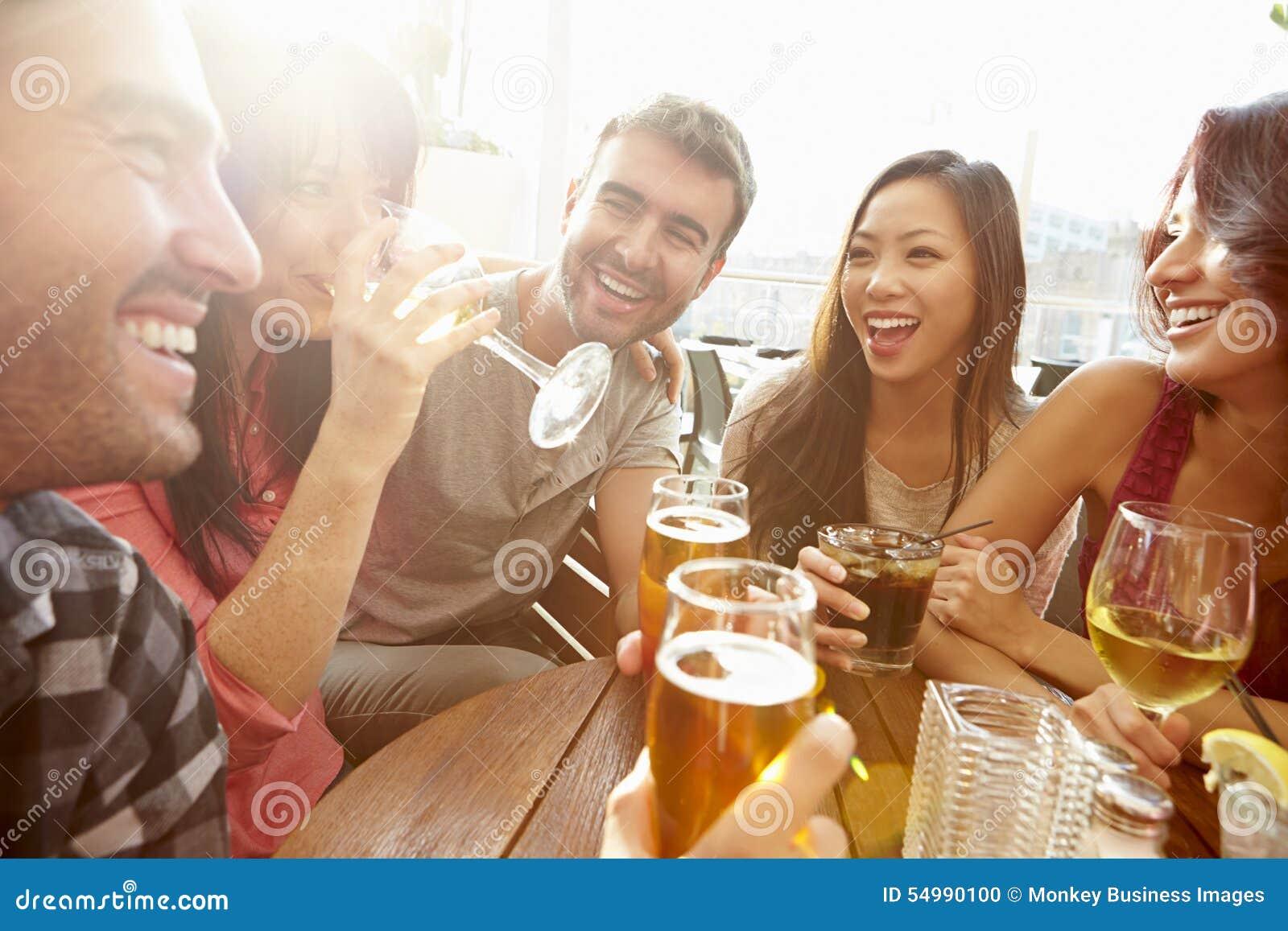 Grupo de amigos que disfrutan de la bebida en la barra al aire libre del tejado