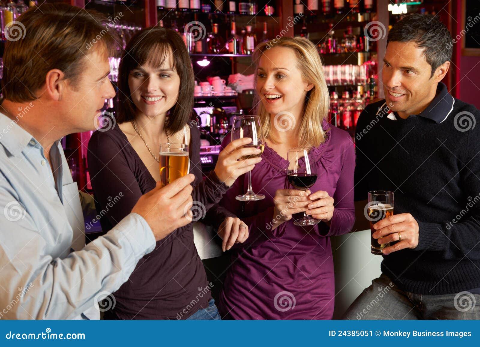 Grupo de amigos que disfrutan de la bebida junto en barra