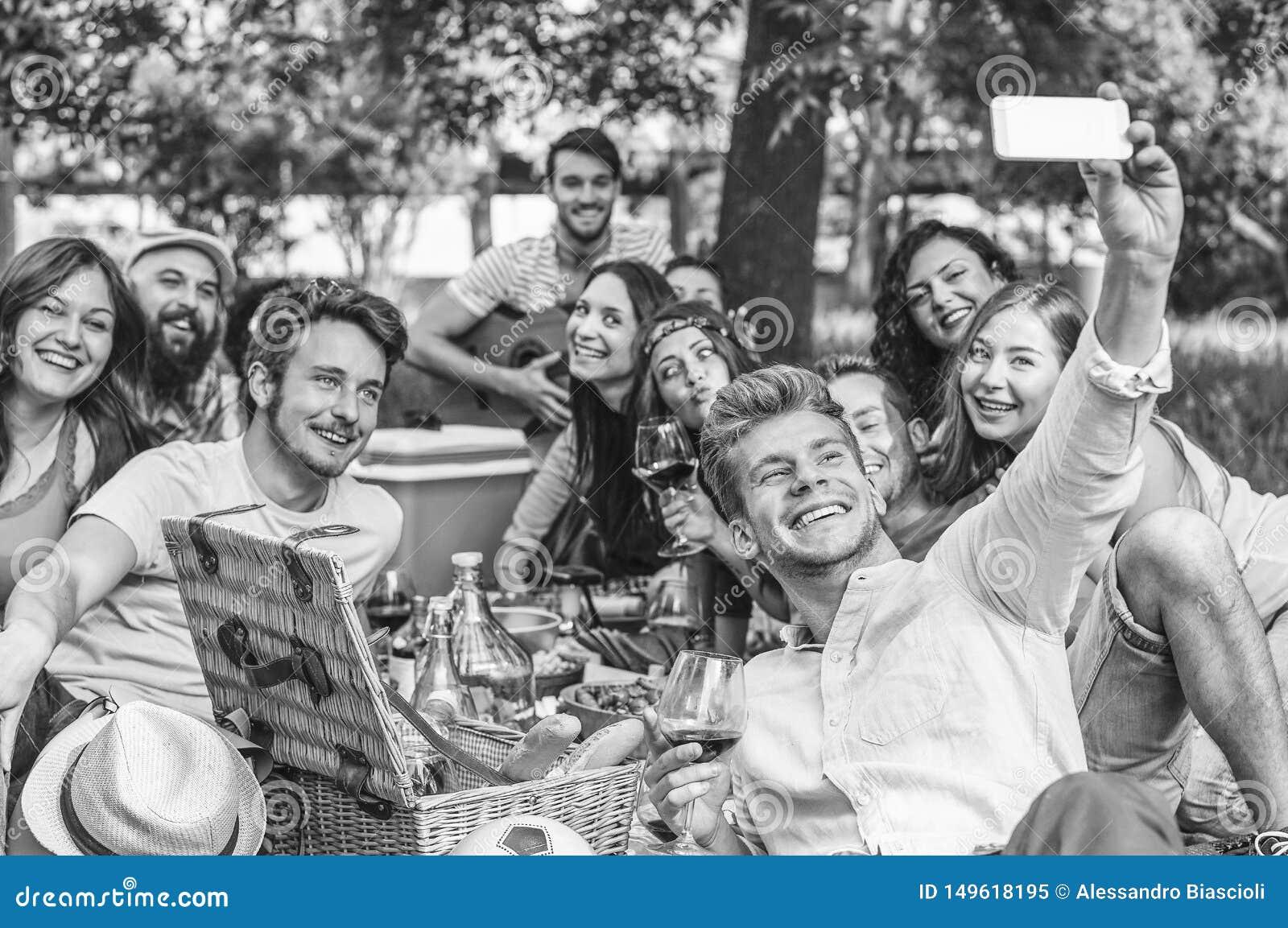 Grupo de amigos que fazem um assado do piquenique e que tomam o selfie com o smartphone m?vel no parque exterior