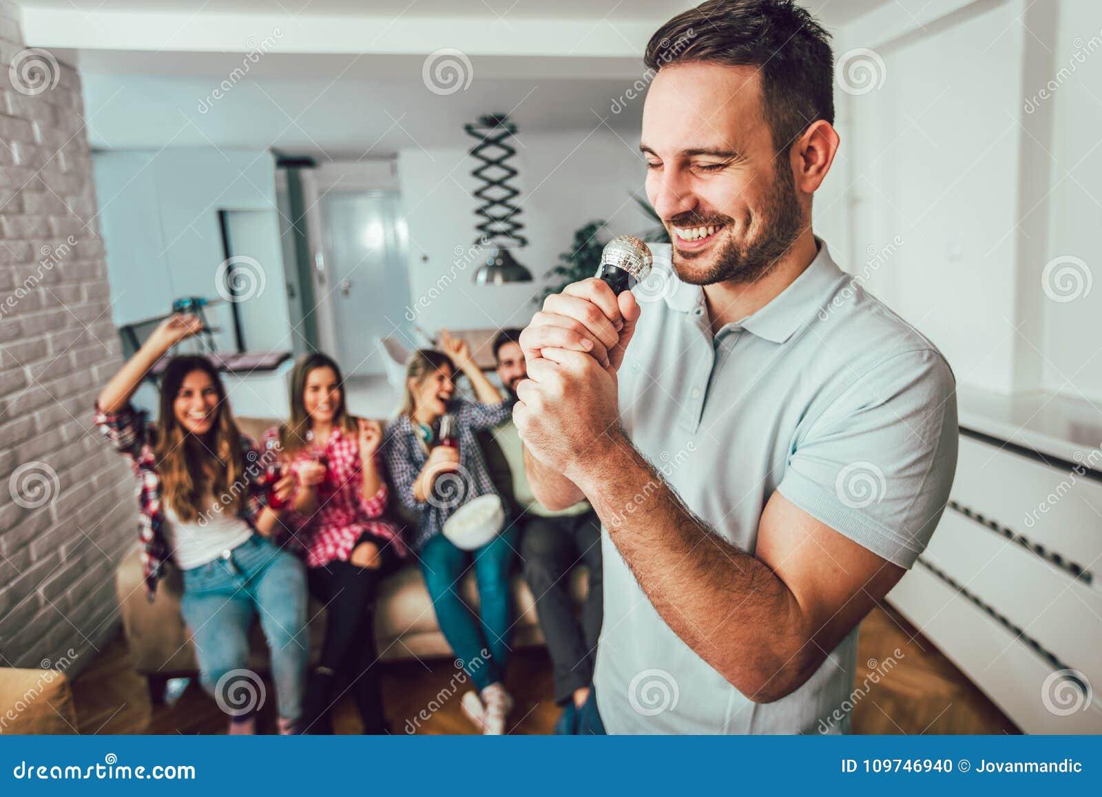 Grupo de amigos que jogam o karaoke em casa