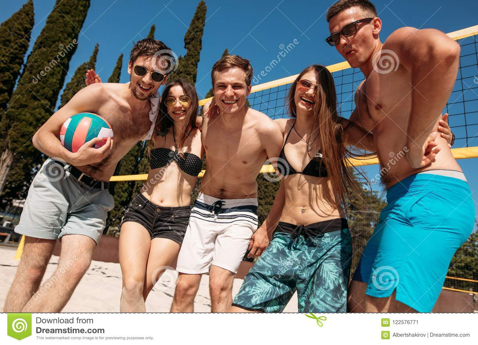 Grupo de amigos que jogam a salva da praia - grupo de pessoas das Multi-éticas que tem o divertimento na praia
