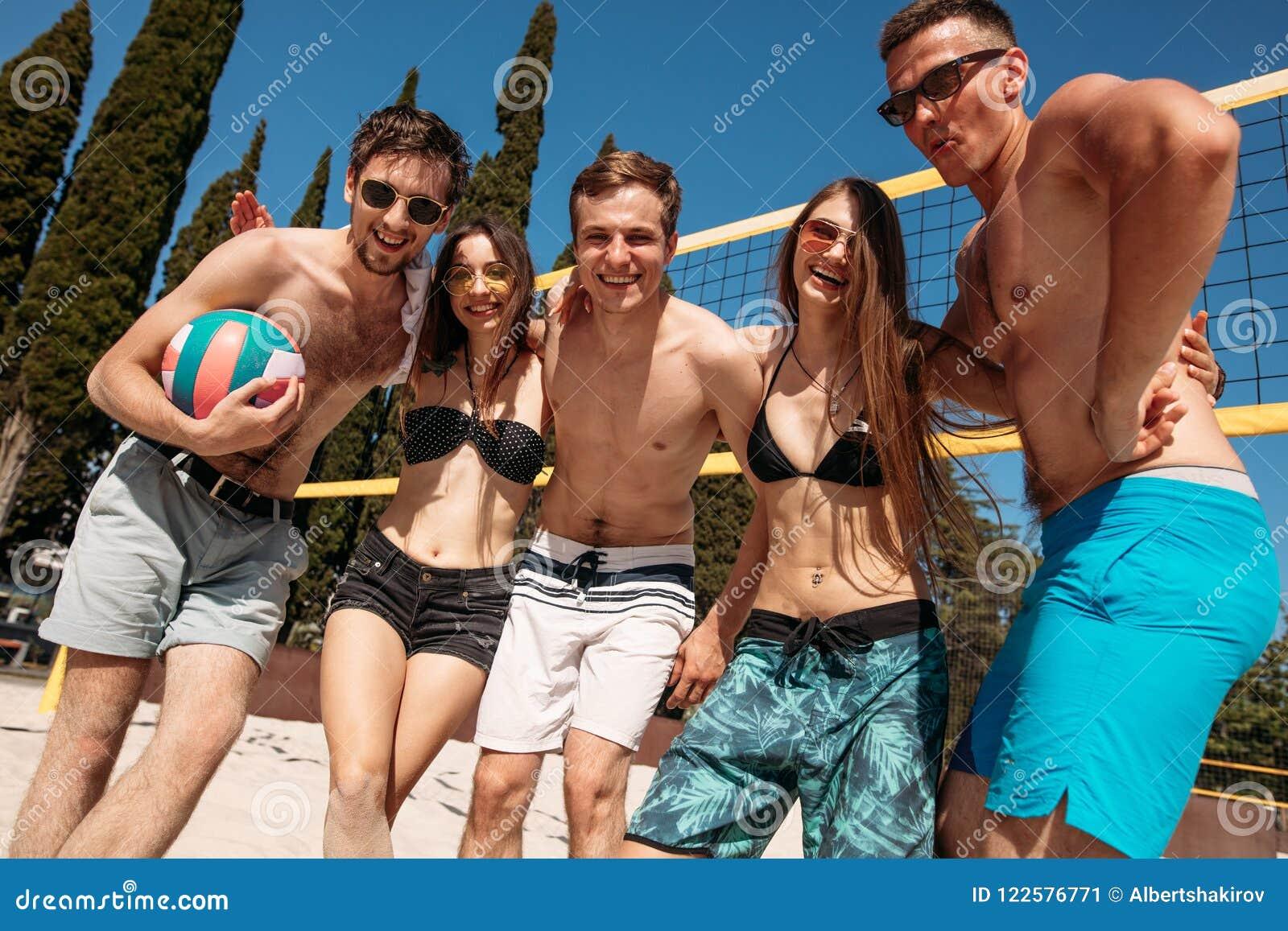 Grupo de amigos que juegan el voleo de la playa - grupo de personas de los Multi-éticas que se divierte en la playa