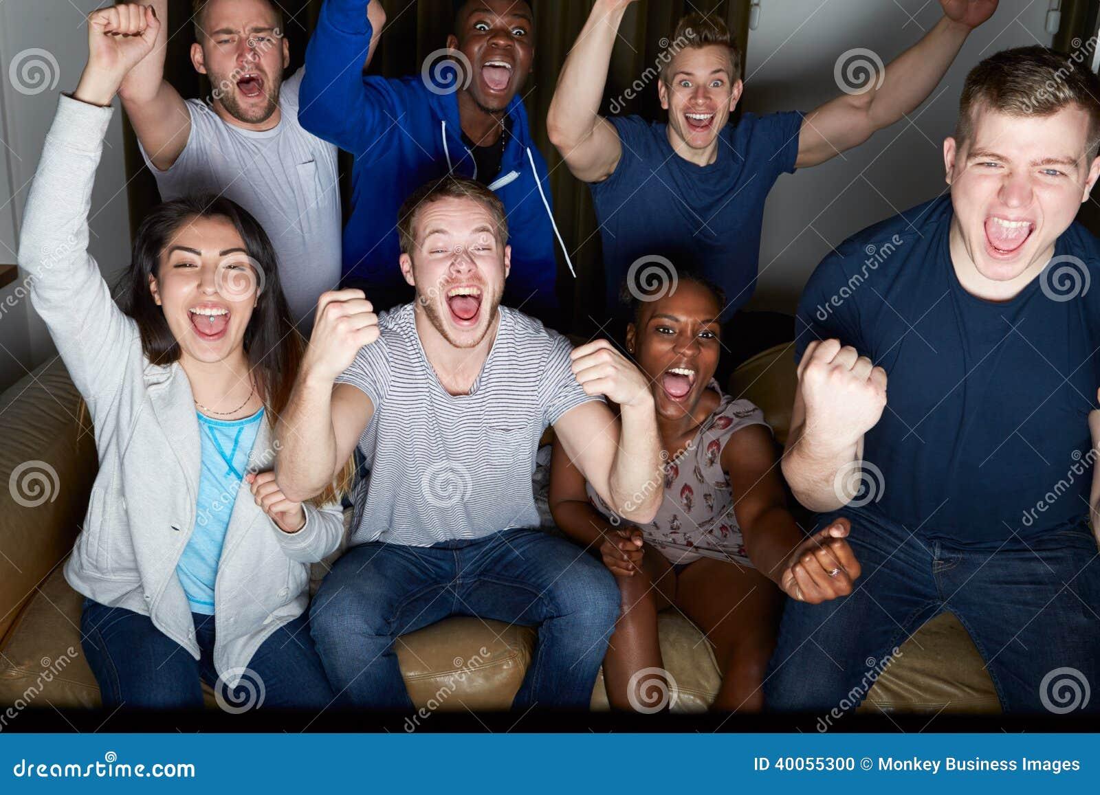 Grupo de amigos que miran la televisión en casa junto