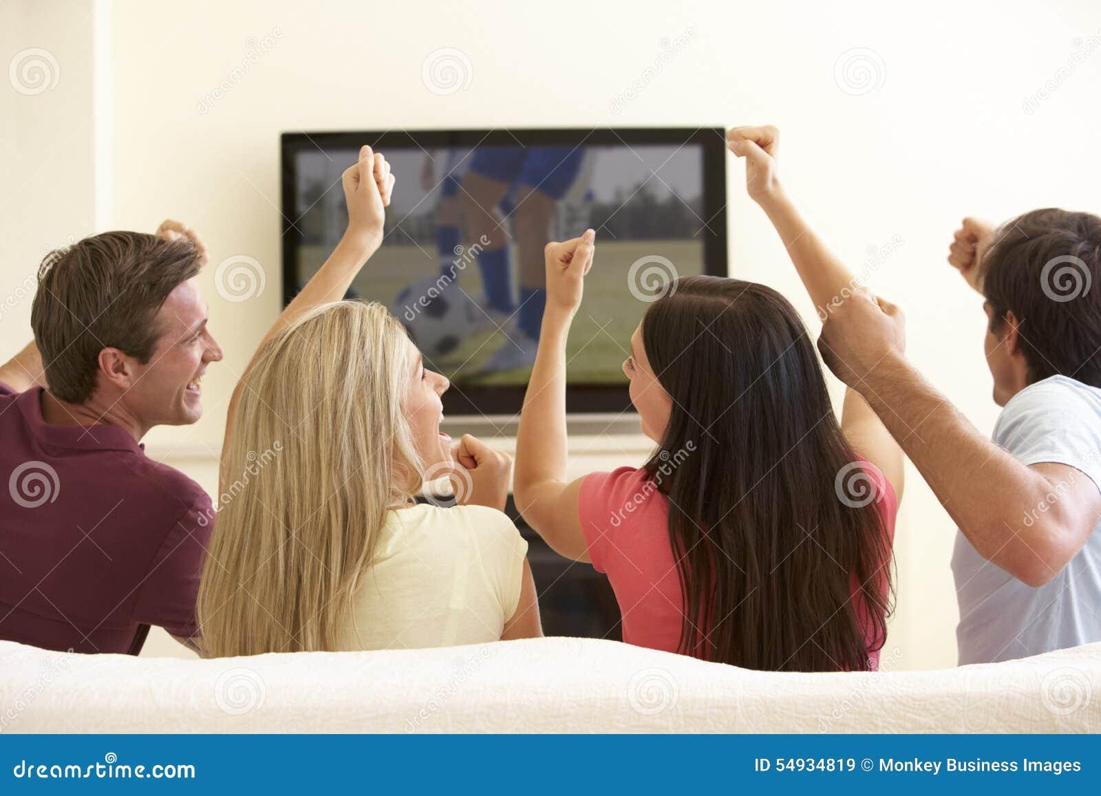 Grupo de amigos que olham a tevê do tela panorâmico em casa