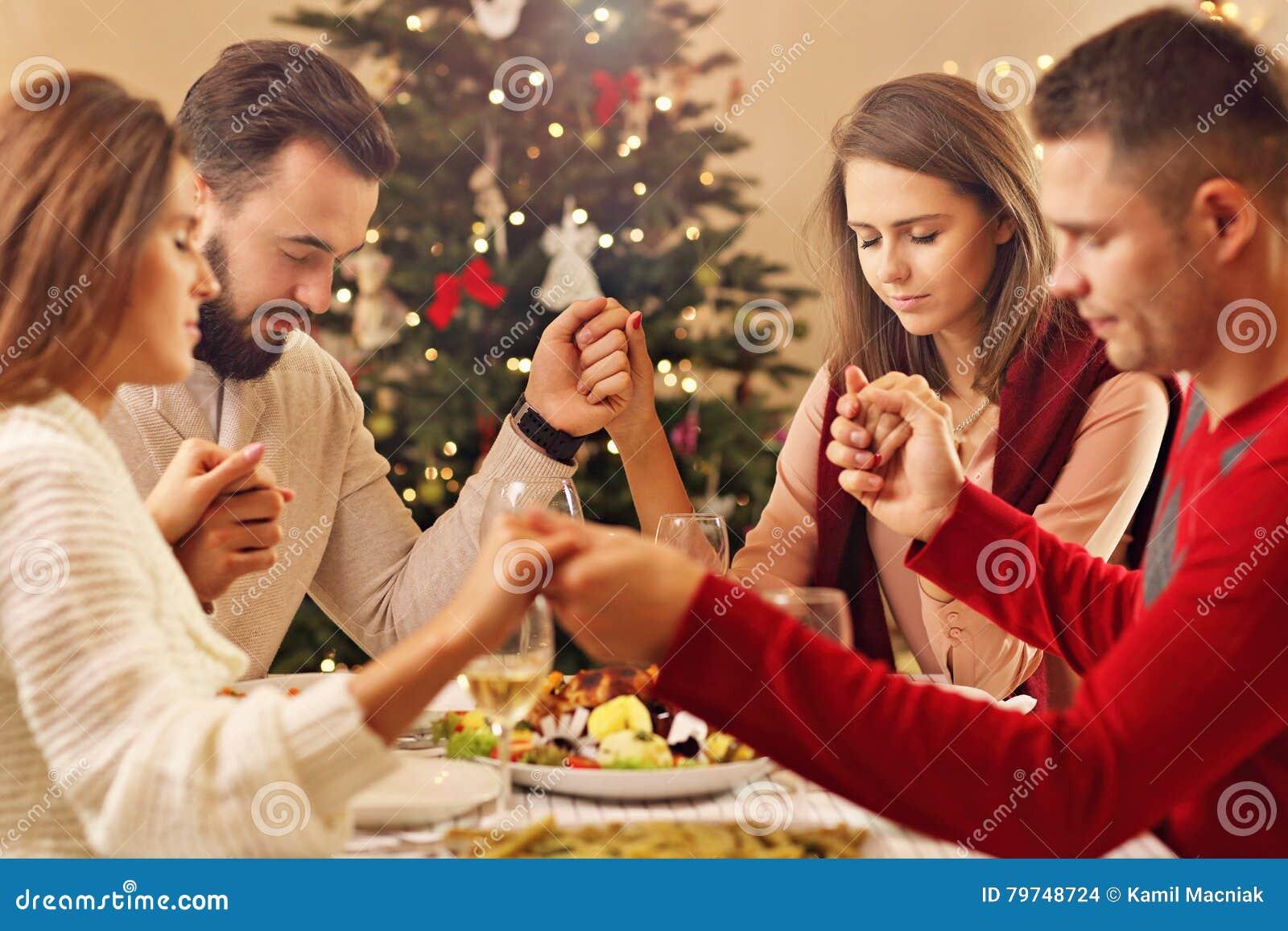 Grupo de amigos que ruegan sobre la tabla de la Navidad