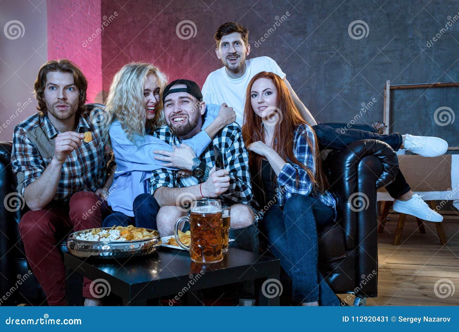 Grupo De Amigos Que Se Divierten En Casa Mirando El Juego Y