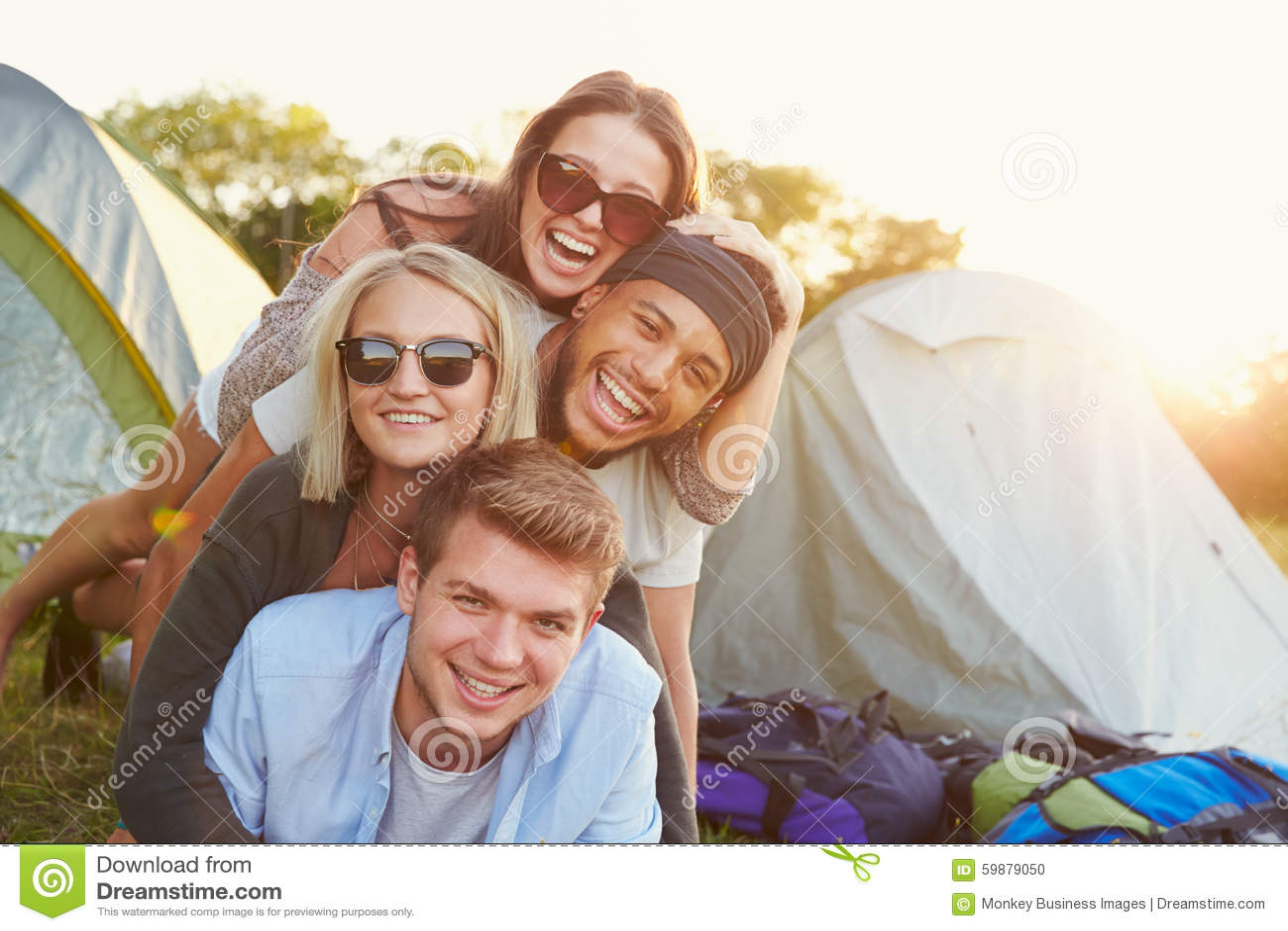 Grupo de amigos que têm o divertimento fora das barracas no feriado de acampamento