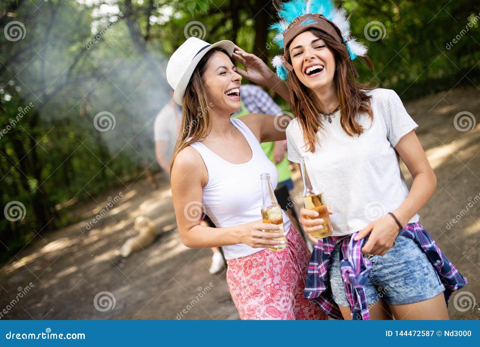 Grupo de amigos que tienen una comida campestre en un parque al aire libre Gente joven feliz que goza del Bbq