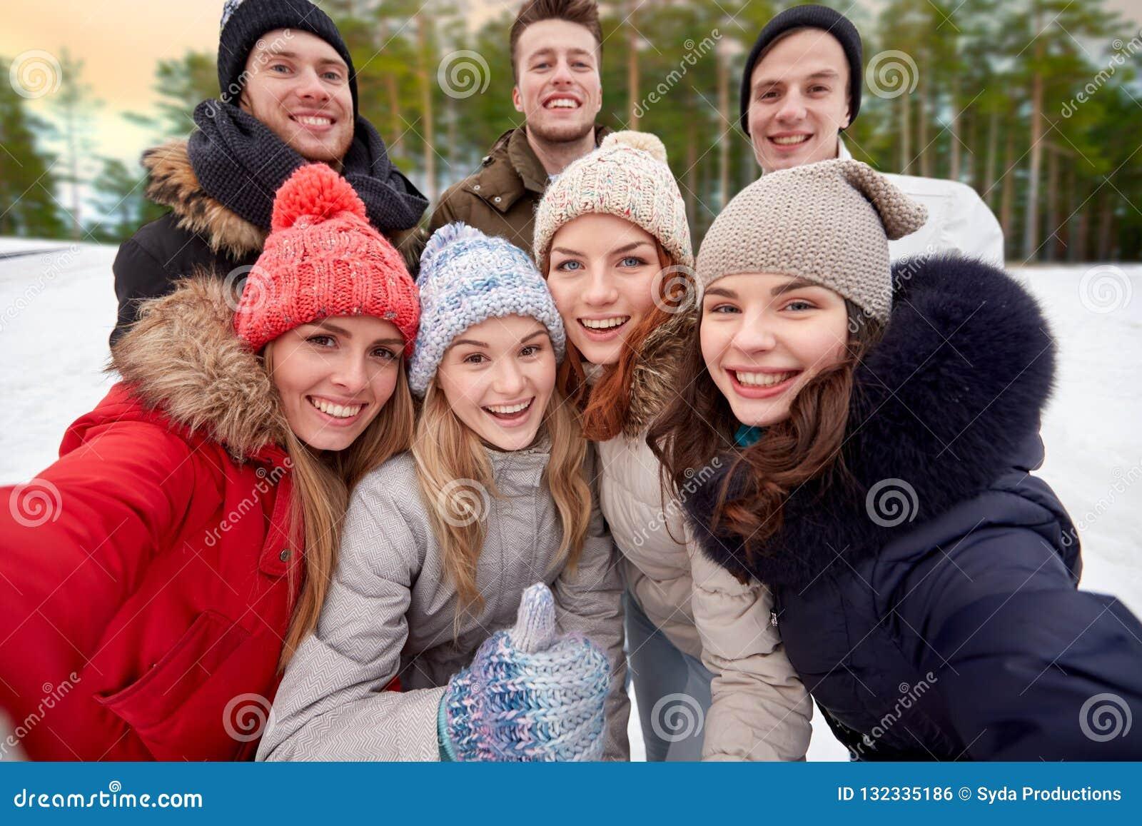 Grupo de amigos que tomam o selfie fora no inverno