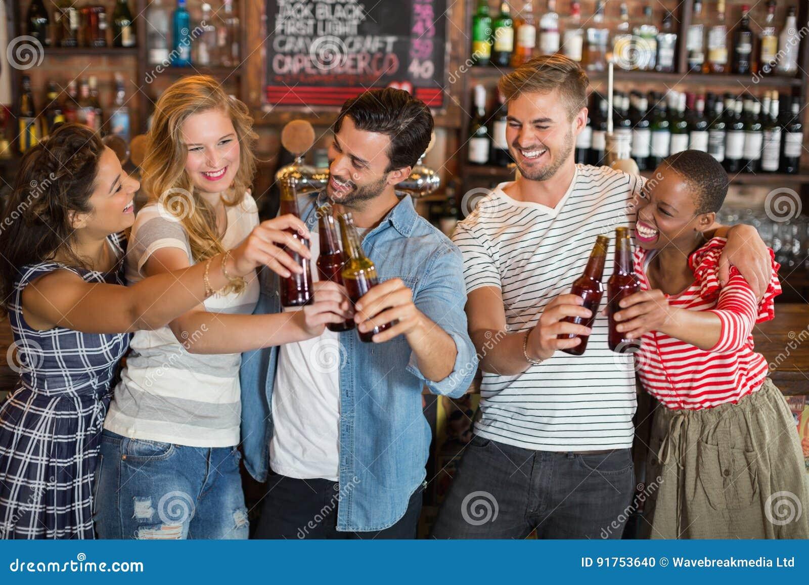 Grupo de amigos que tuestan las botellas de cerveza en el pub