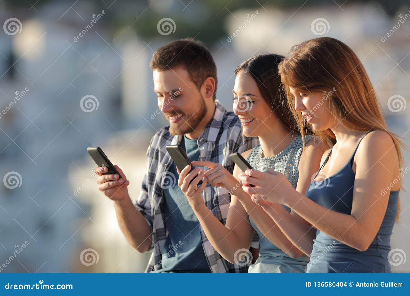 Grupo de amigos que usam seus telefones espertos